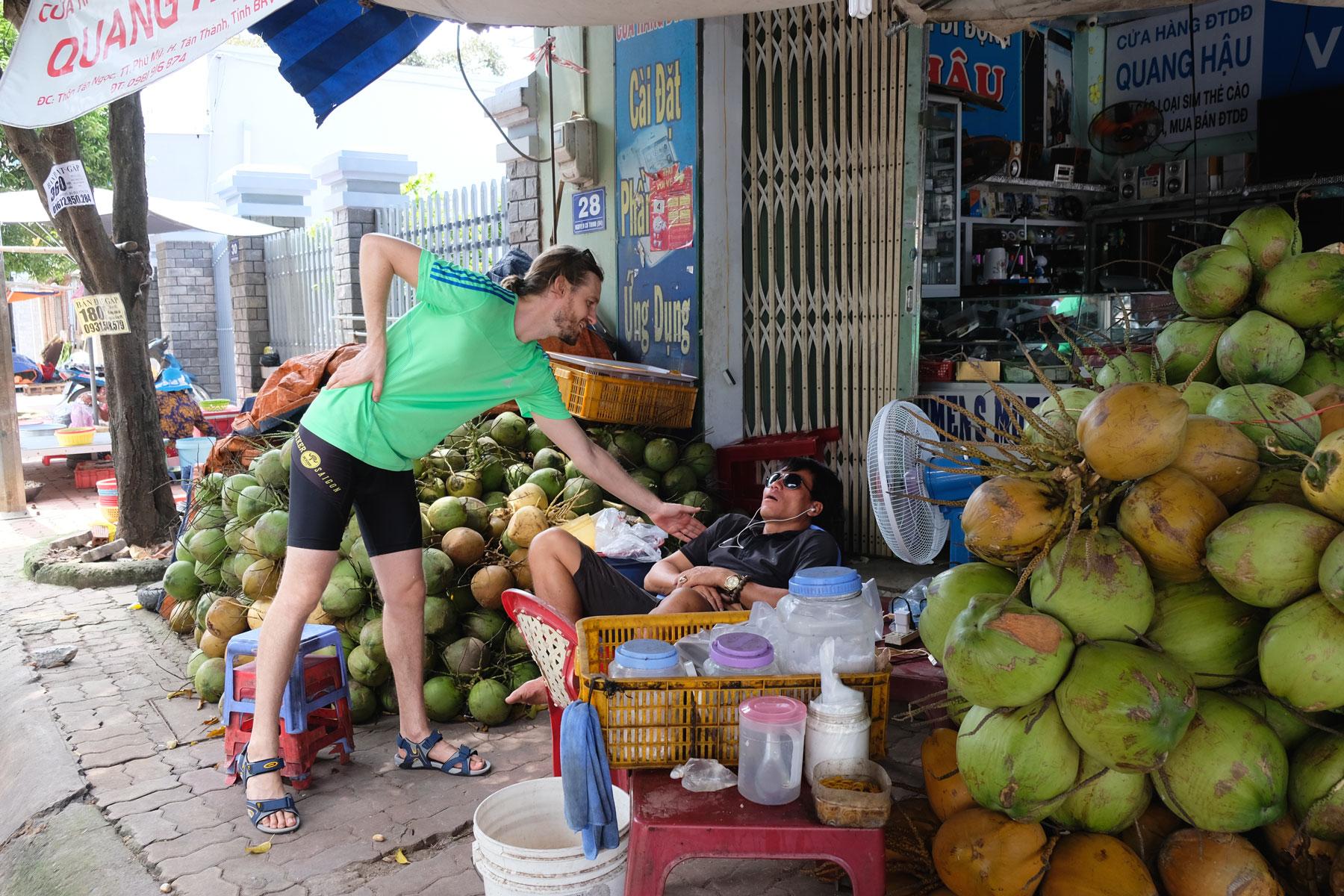 Sebastian weckt den Verkäufer von Kokosnüssen auf, der in seinem Stuhl sitzend schläft.