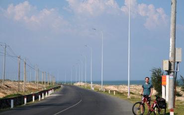 Sebastian steht mit seinem Fahrrad an der ruhigen Küstestraße im Süden Vietnams.