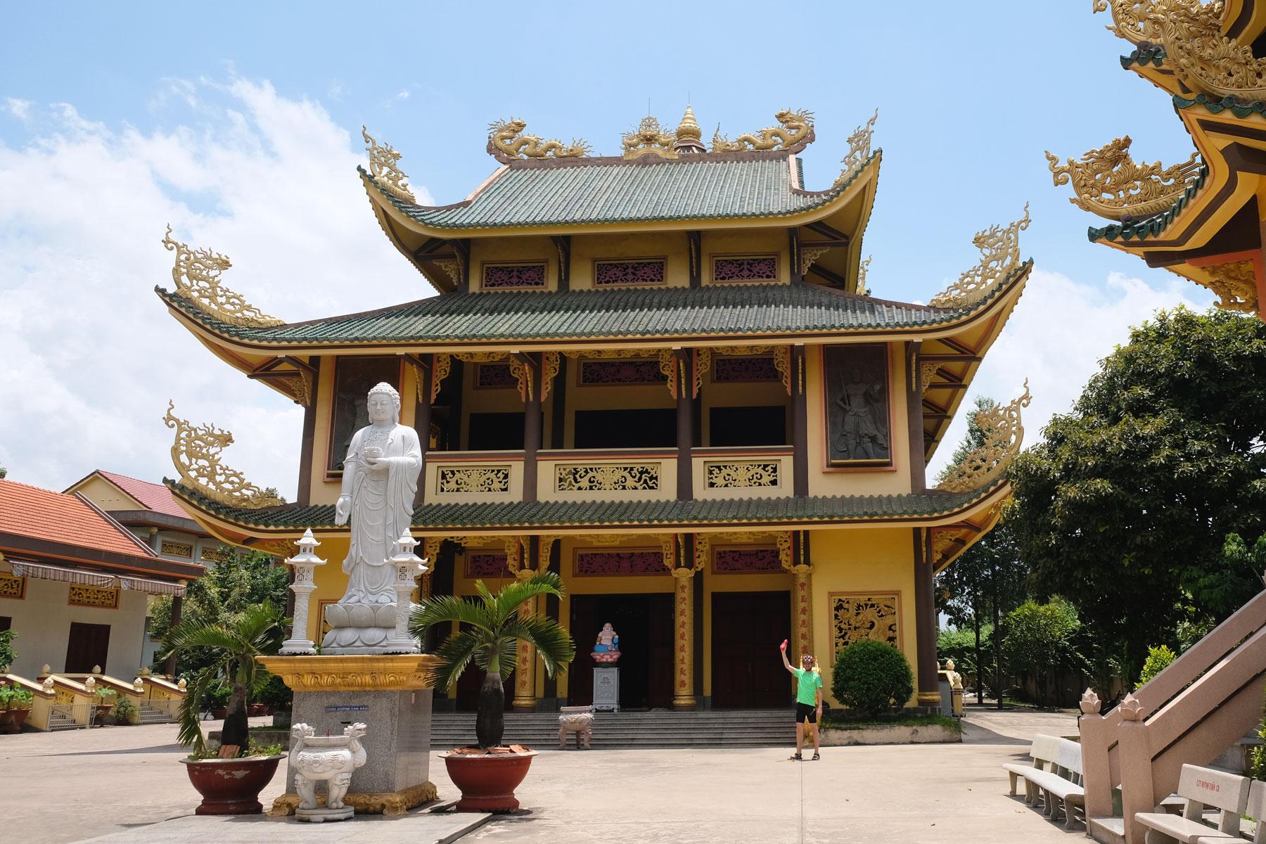 Sebastian steht vor einem Tempel im Süden Vietnams.