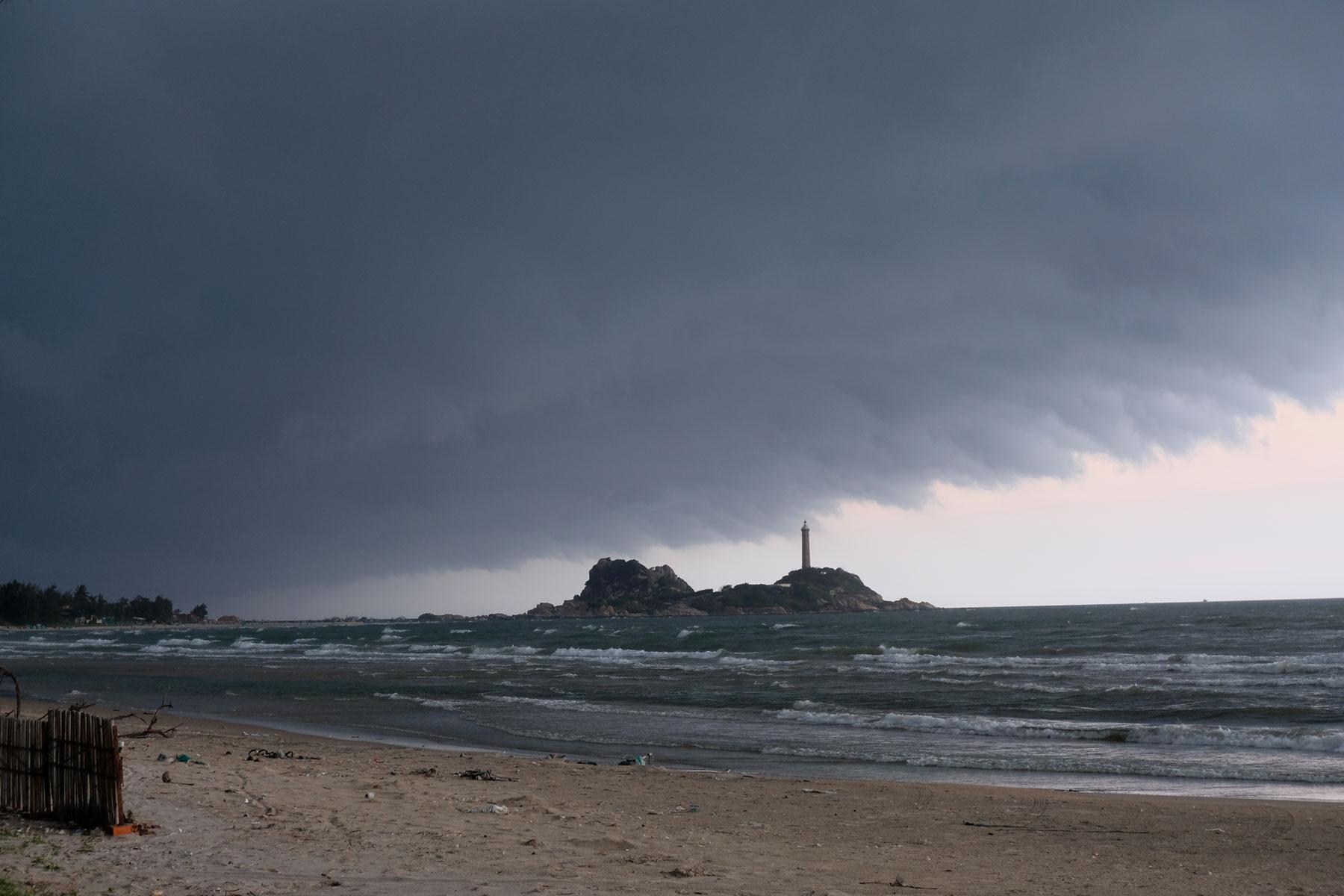 Dunkle Monsunwolken hängen über dem Leuchtturm von Văn Kê in Vietnam.