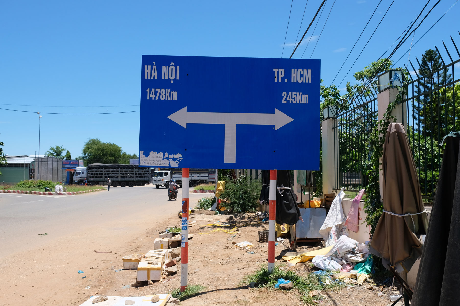Ein Straßenschild informiert über die Entfernung in die vietnamesische Hauptstadt Hanoi und die größte Stadt Ho-Chi-Minh-City.