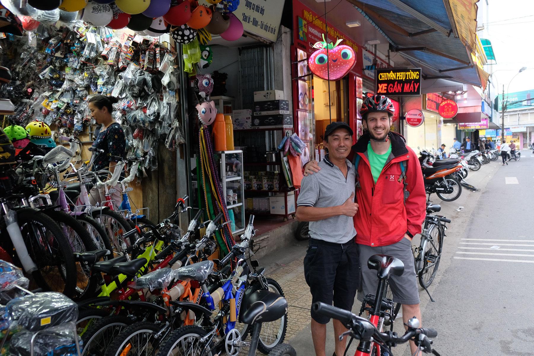 Sebastian steht mit Dinh vor einem vietnamesischen Fahrradgeschäft.