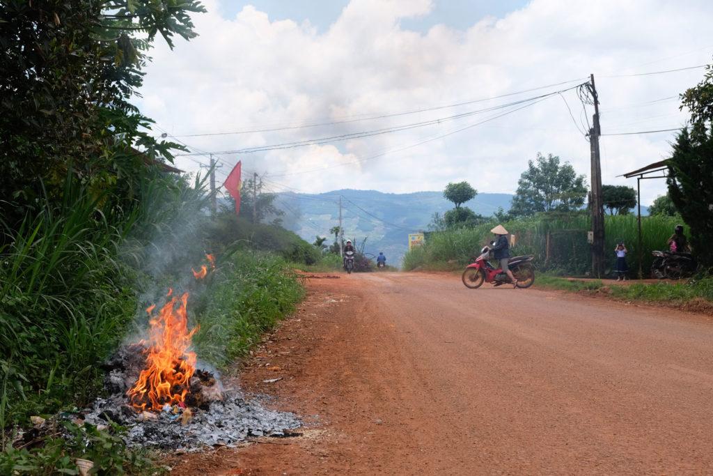 Auf einer kleinen Straße wird Plastikmüll im Feuer verbrannt.