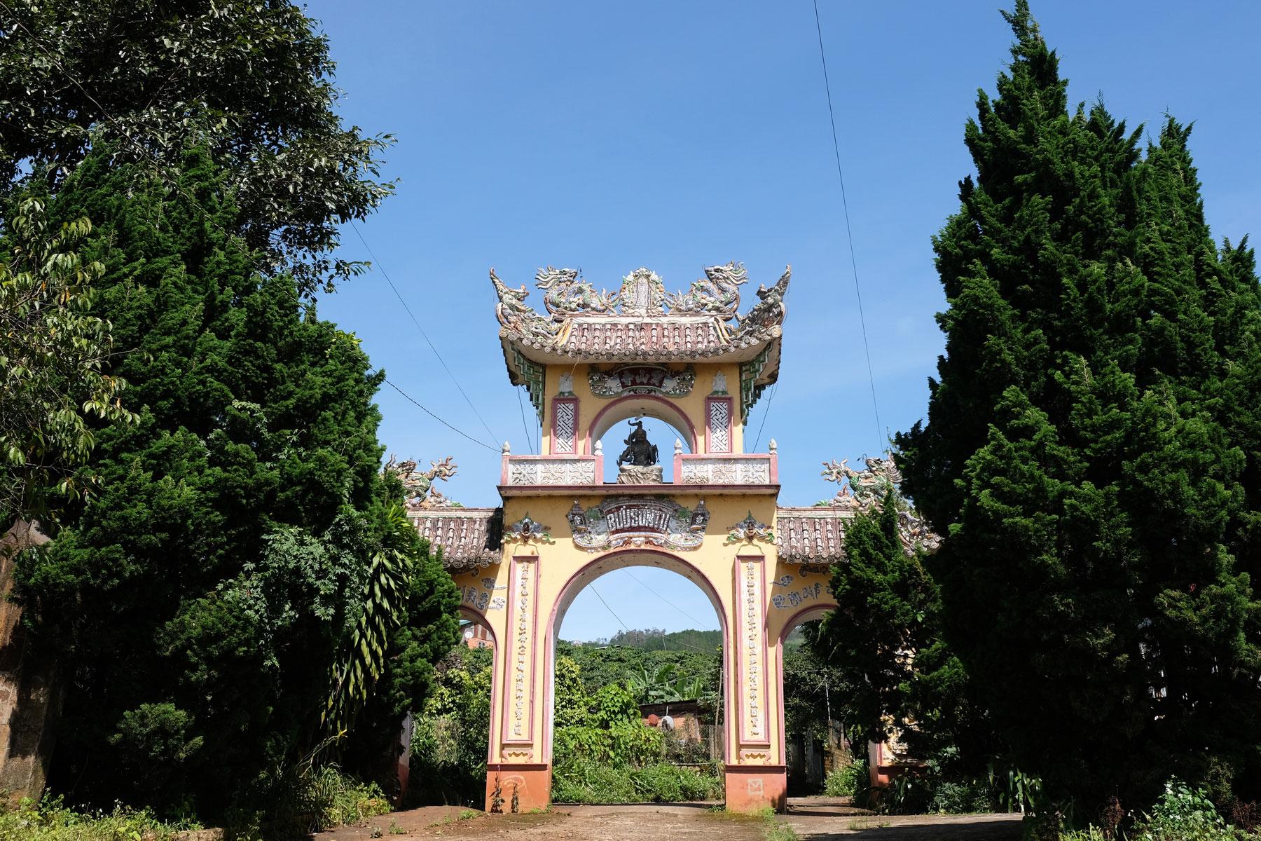 Ein vietnamesisches Tor steht zwischen zwei großen Bäumen.