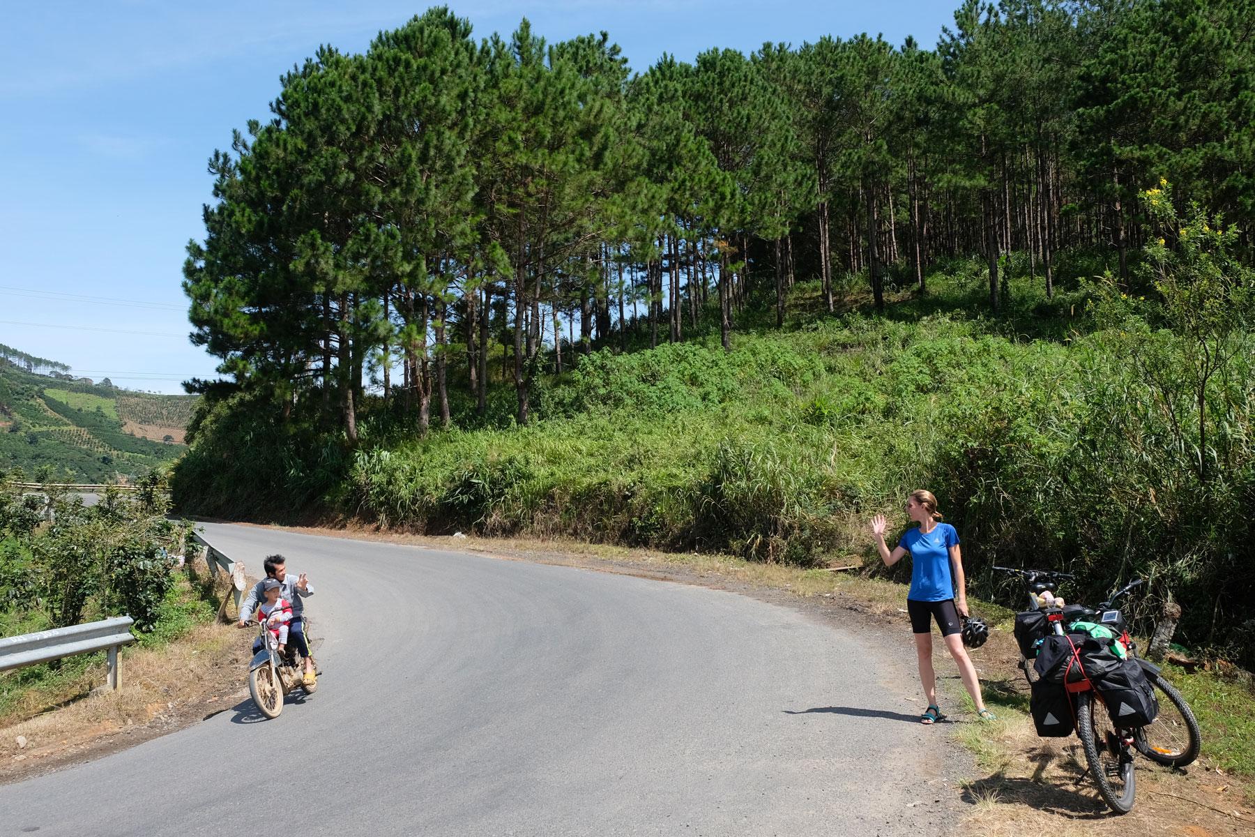 Leo steht auf der Straße, ein Mann fährt mit seinem Sohn auf dem Motorrad vorbei und winkt.