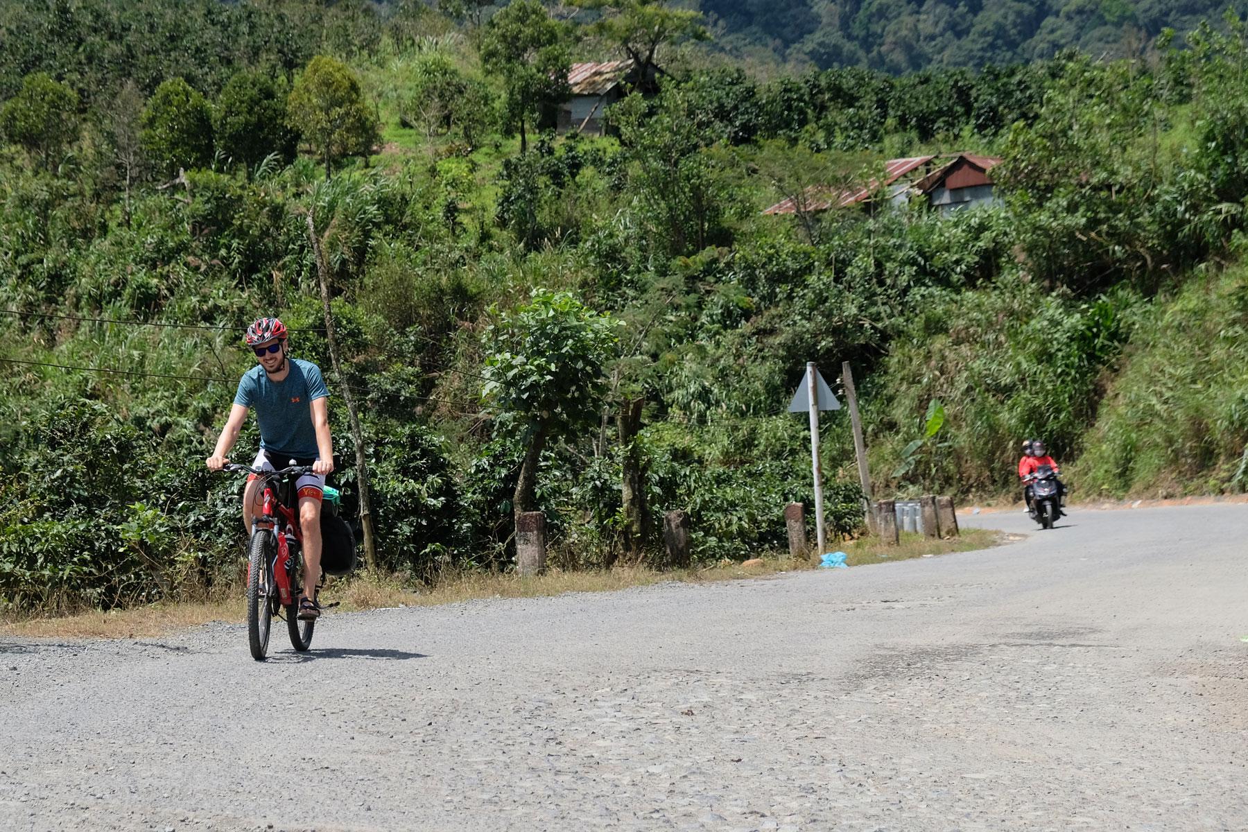 Sebastian fährt auf dem Fahrrad über eine holprige Straße
