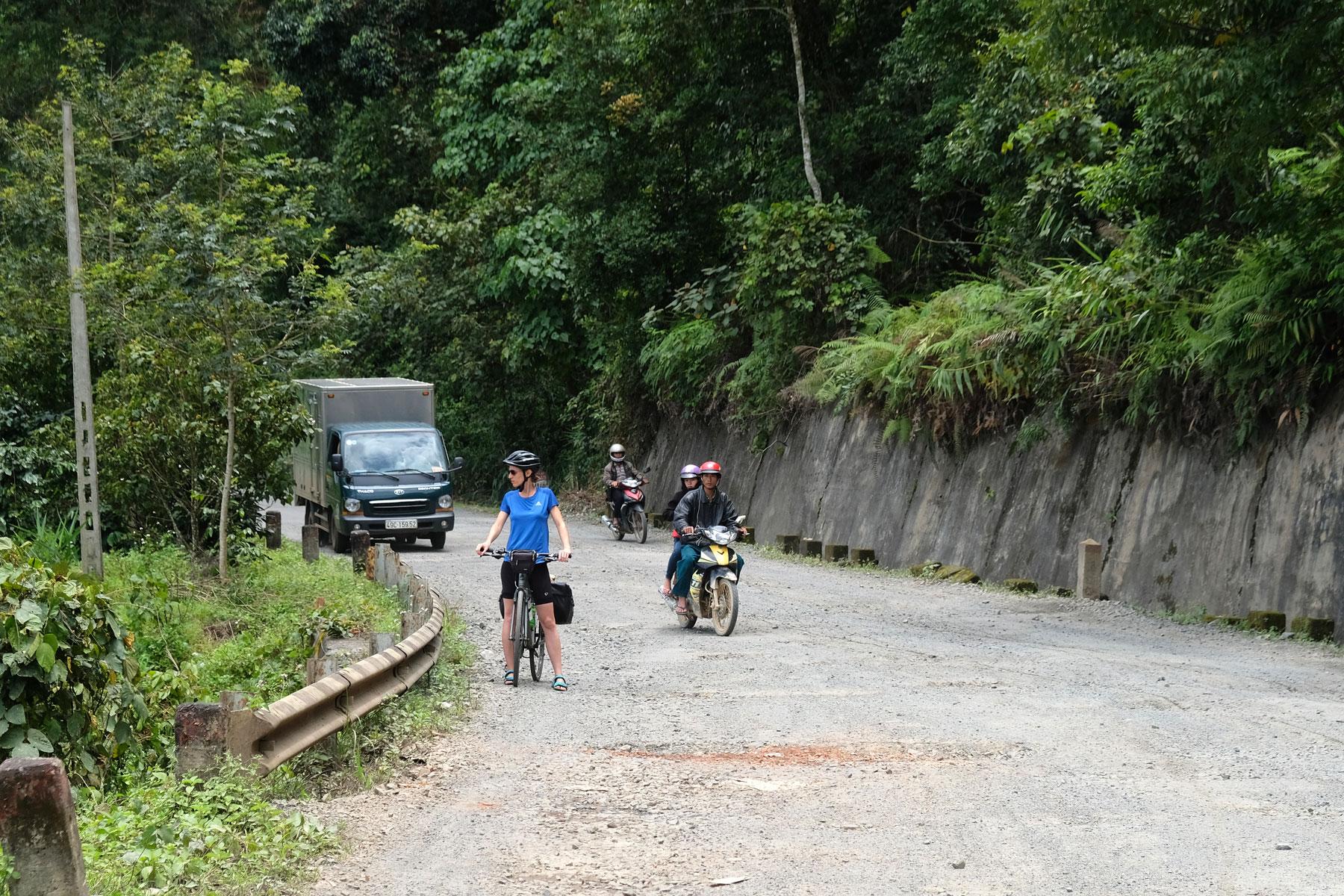 Leo steht mit ihrem Fahrrad am Straßenrand, neben ihr fahren Motorräder und ein kleiner Lastwagen vorbei.