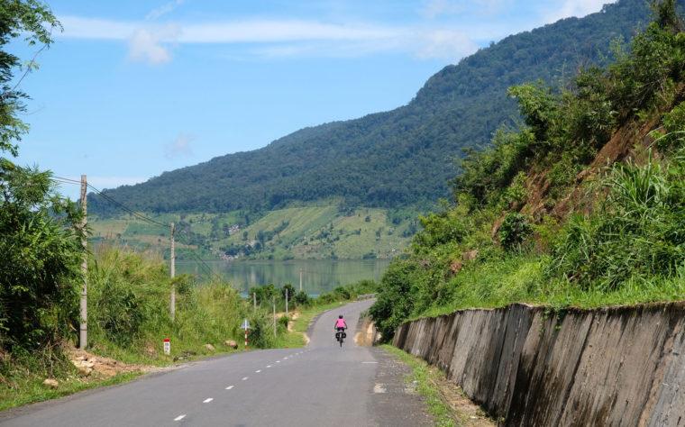 Leo fährt mit ihrem Fahrrad einen Berg im Hochland Vietnams hinunter.