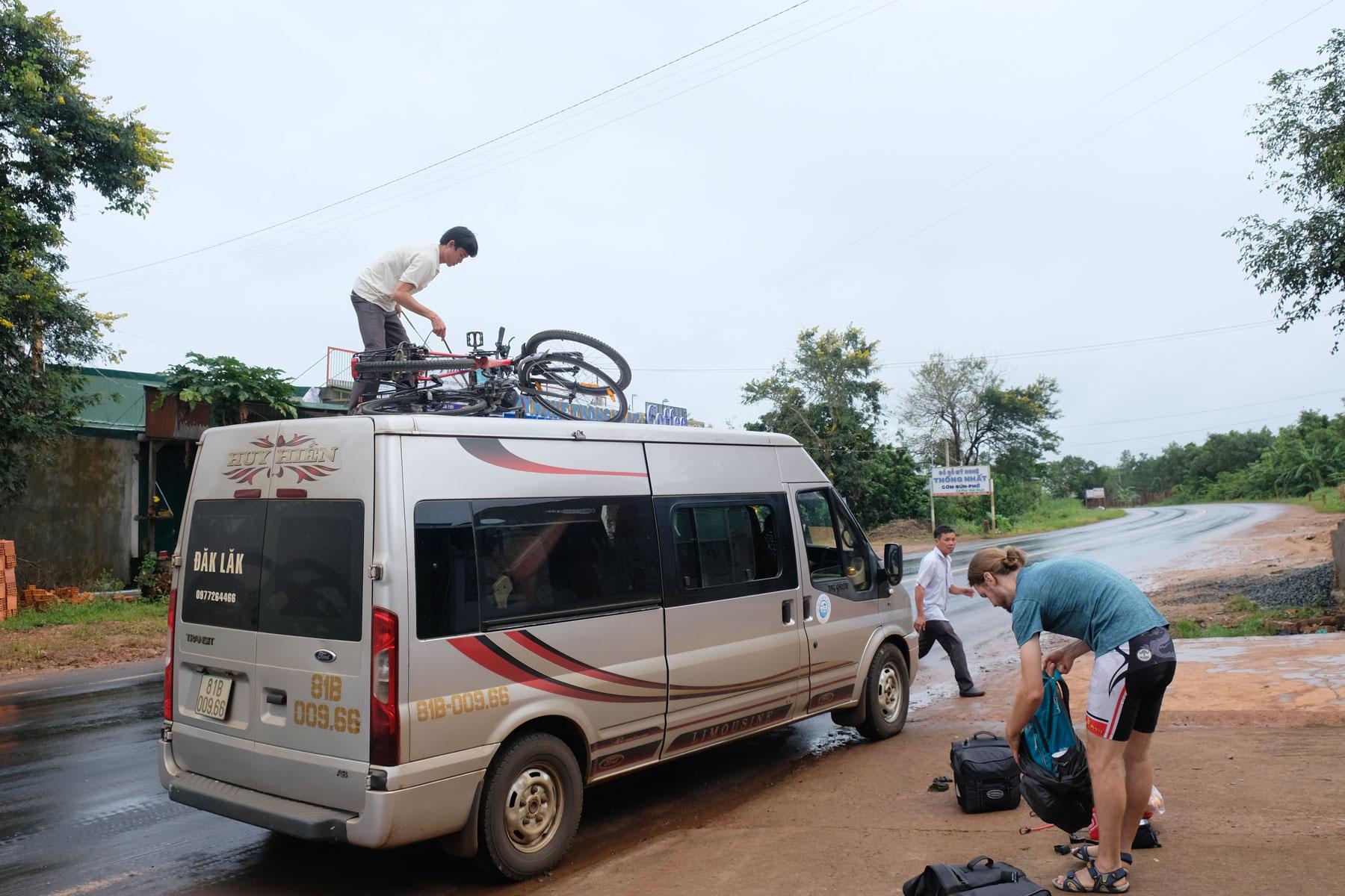 Ein Mann bindet unsere Fahrräder auf dem Busdach fest, Sebastian räumt unser Gepäck ins Innere des Busses.
