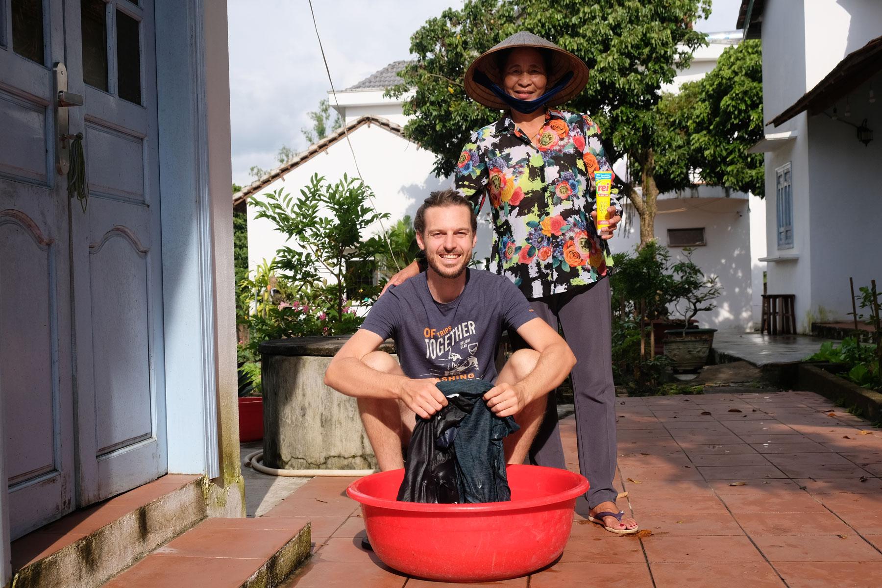 Sebastian wäscht seine Wäsche, neben ihm steht unsere vietnamesische Gastgeberin aus unserem Homestay in Kon Tum.