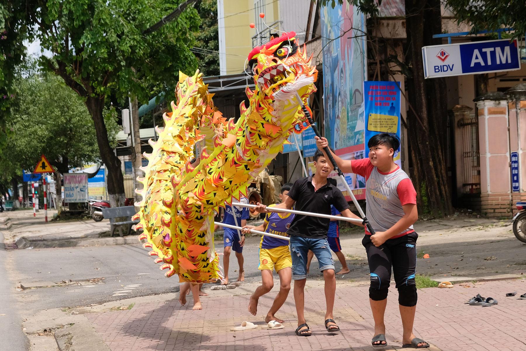Jungen balancieren einen großen Papierdrachen auf langen Stöcken in Vietnam.