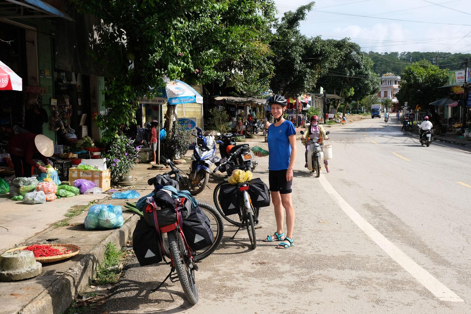 Leo steht mit den beiden Fahrrädern an Straßenständen an der Straße in Vietnam.