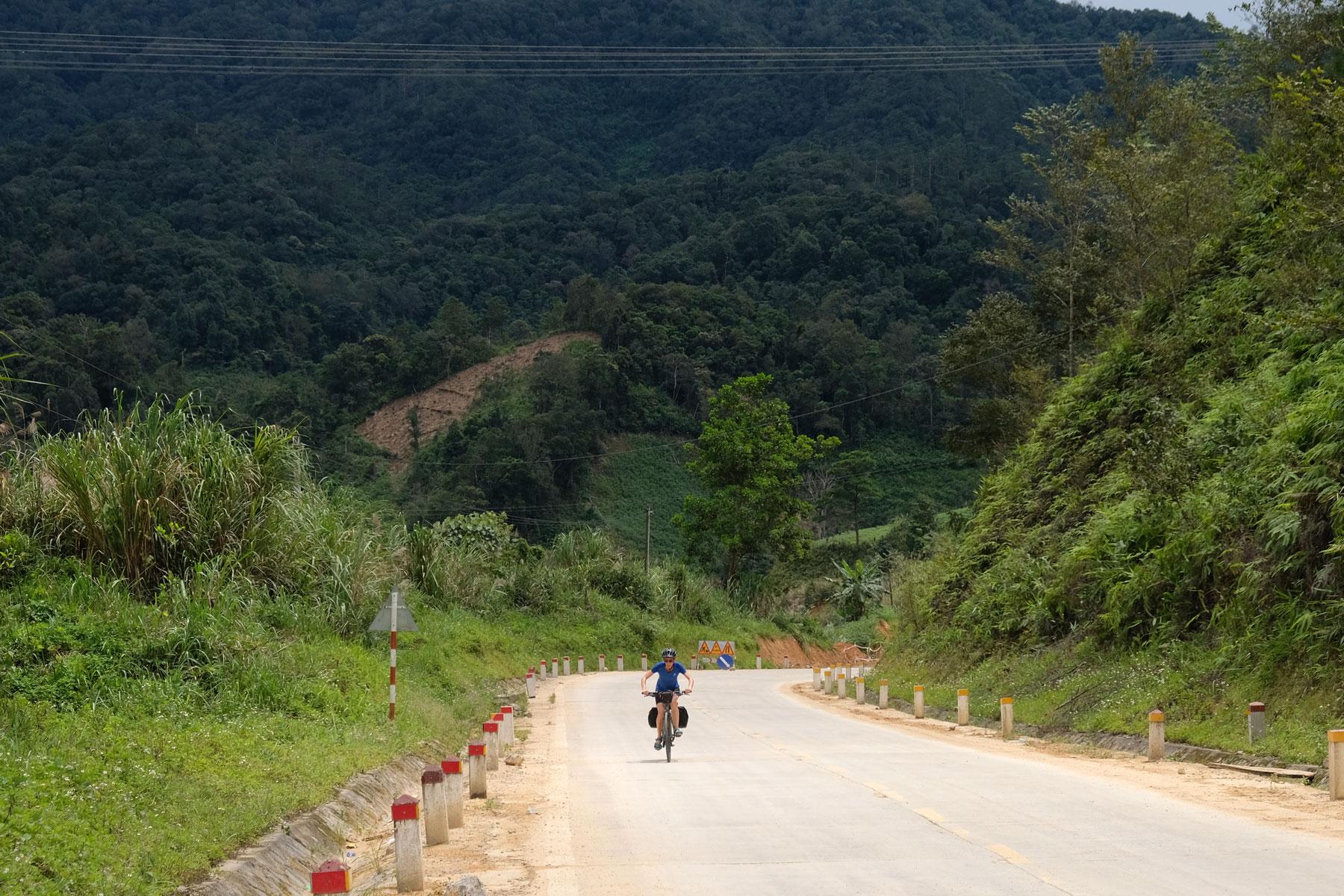 Leo kämpft sich mit ihrem Fahrrad den Berg im Hochland Vietnams hinauf.