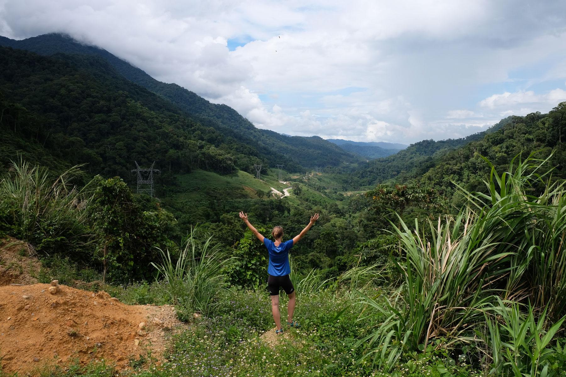 Leo steht mit ausgebreiteten Armen in den Bergen Vietnams.