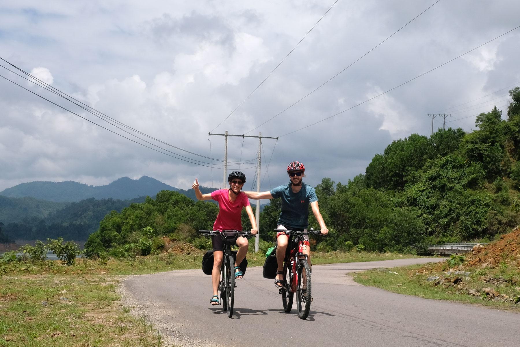 Leo und Sebastian fahren mit ihren Fahrrädern auf einer Straße im Hochland Vietnams.