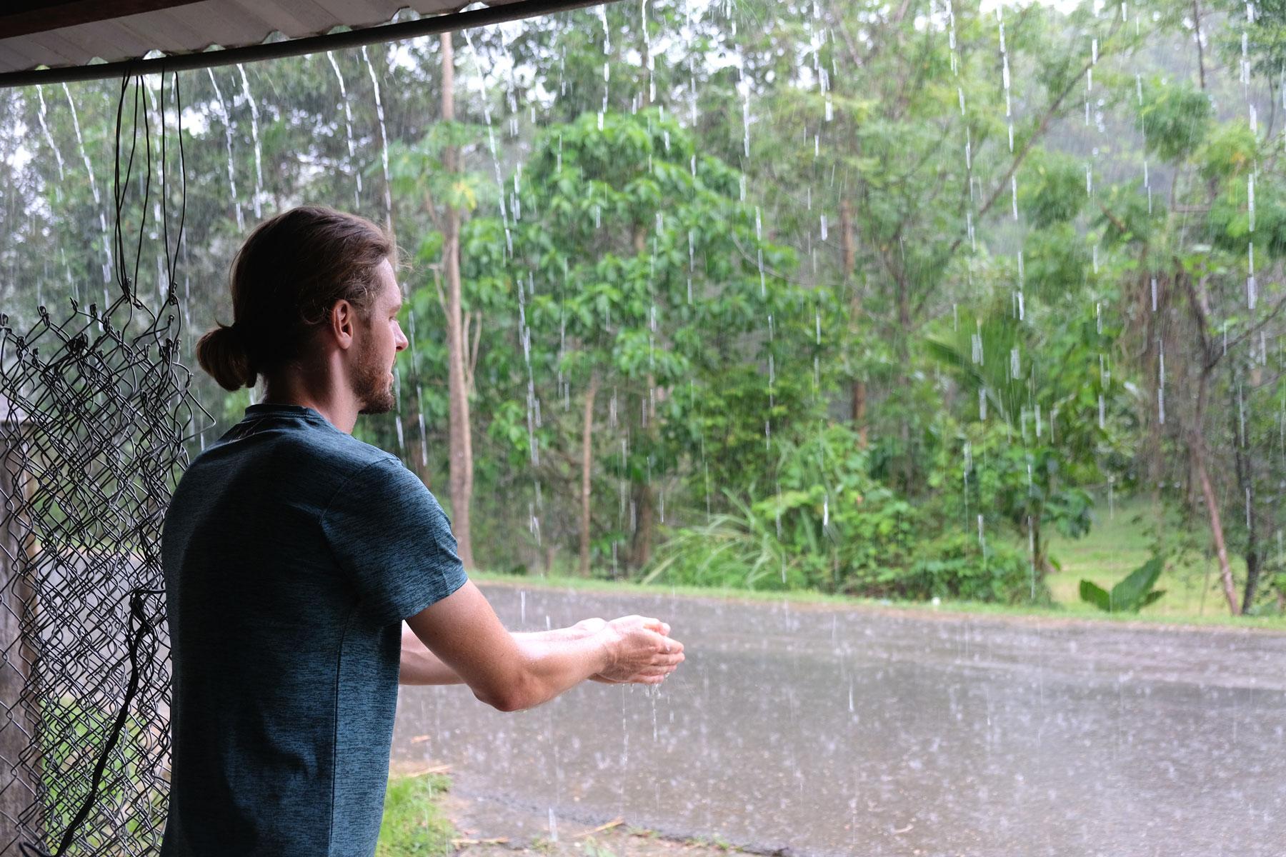 Sebastian steht unter einem Dach und wäscht sich seine Hände am vom Dach strömenden Regenwasser.