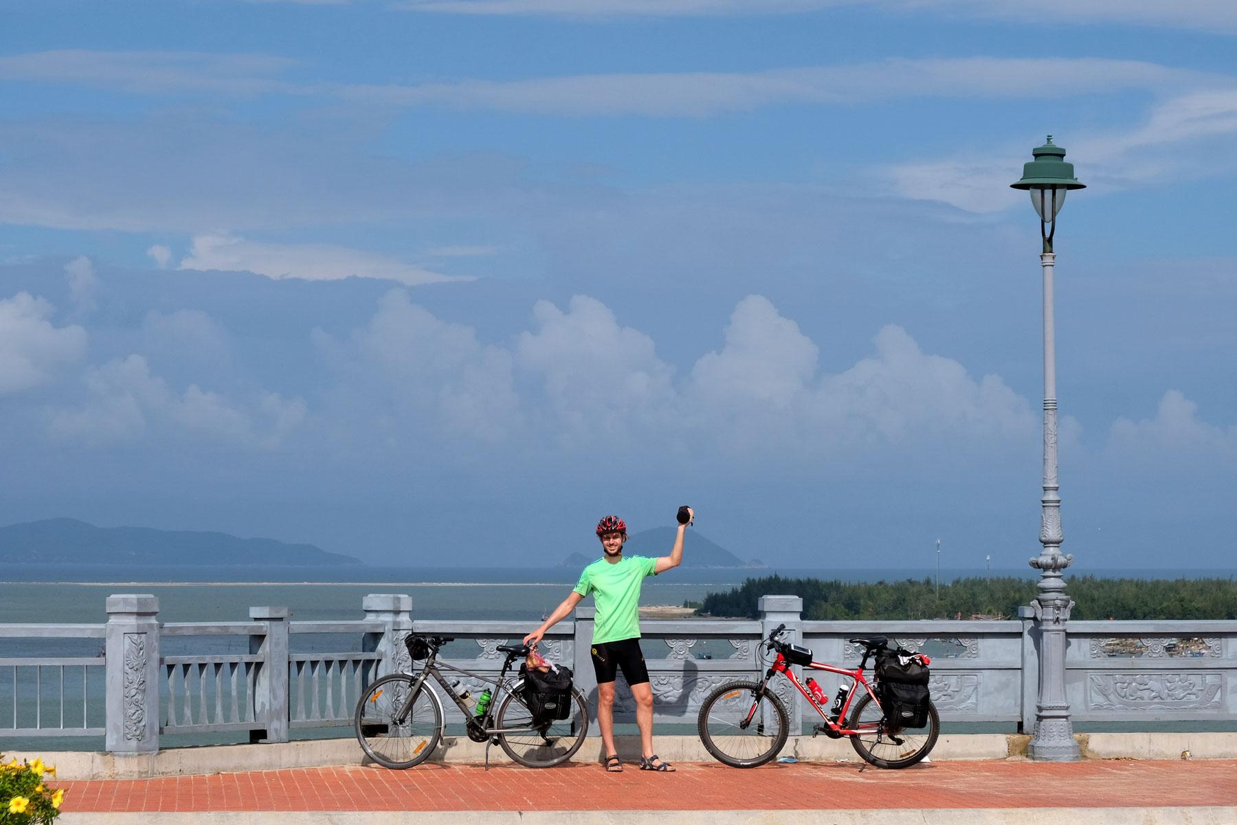 Sebastian steht mit den zwei Fahrrädern auf der großen Brüce vor Hoi An in Vietnam, hinter ihm das Meer.