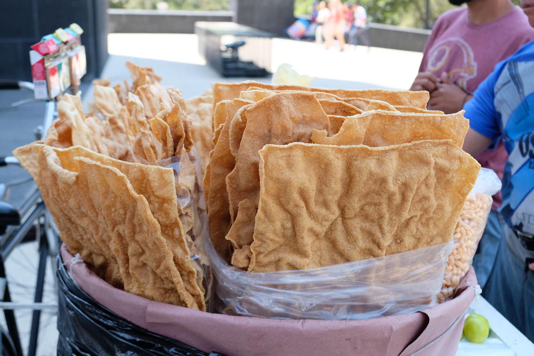 Verkäufer bieten große Platten von Chicharon an.