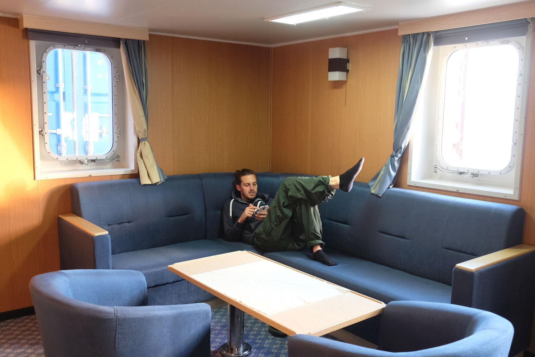 Sebastian liegt im Aufenthaltsraum für Passagiere auf einem Sofa.