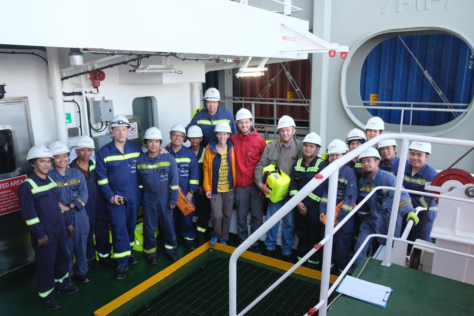 Leo und Sebastian zusammen mit der Besatzung des Containerschiffs CMA CGM Jacques Joseph.