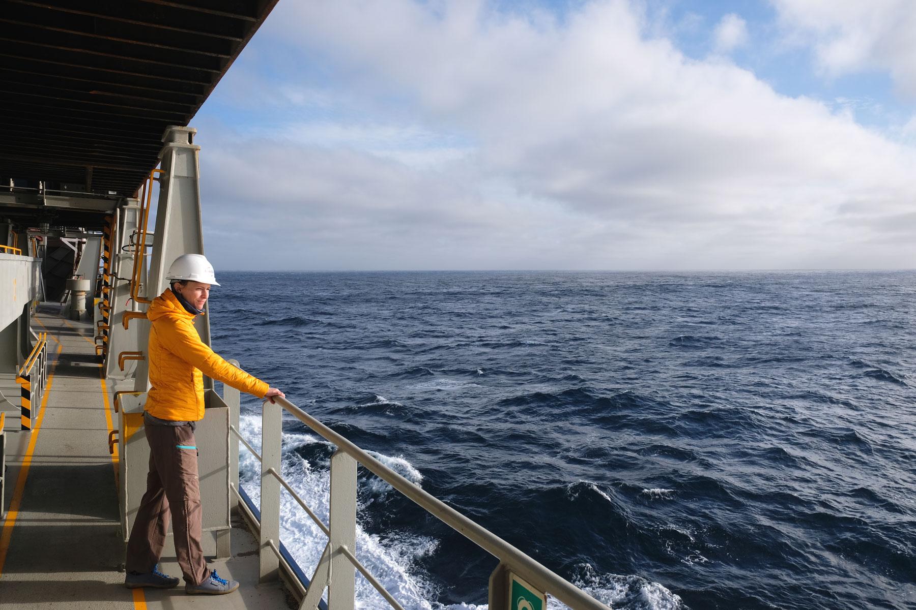 Leo schaut über die Reling eines Frachtschiffs auf den Pazifik.