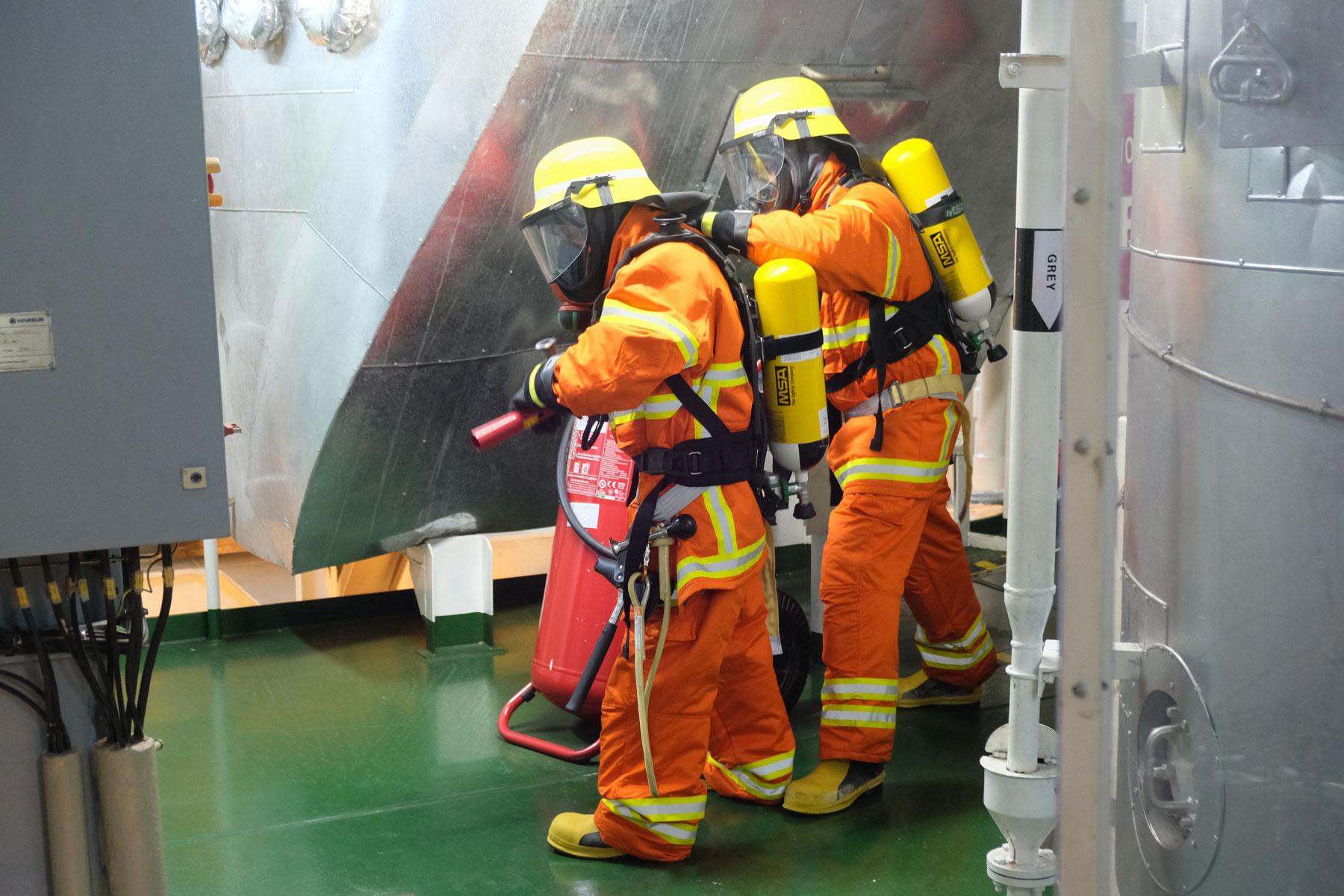 Zur Feuerbekämpfung ausgebildete Crew-Mitglieder bei einer Brandschutzübung.