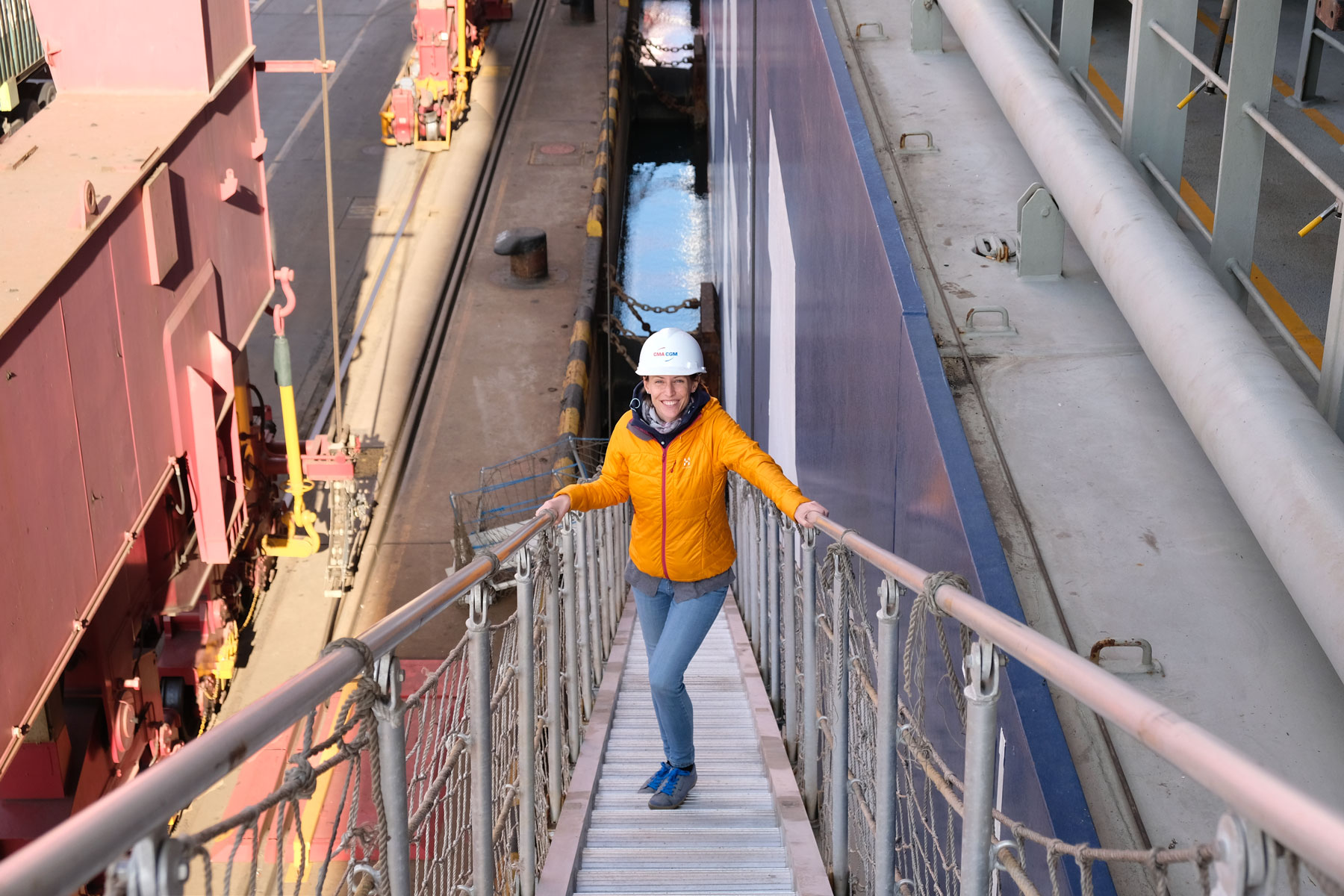 Leo betritt am Hafen von Qingdao über eine Gangway ein Containerschiff.