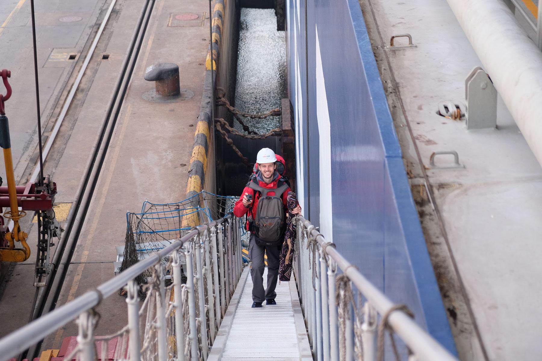 Sebastian betritt am Hafen von Qingdao über eine Gangway ein Containerschiff.