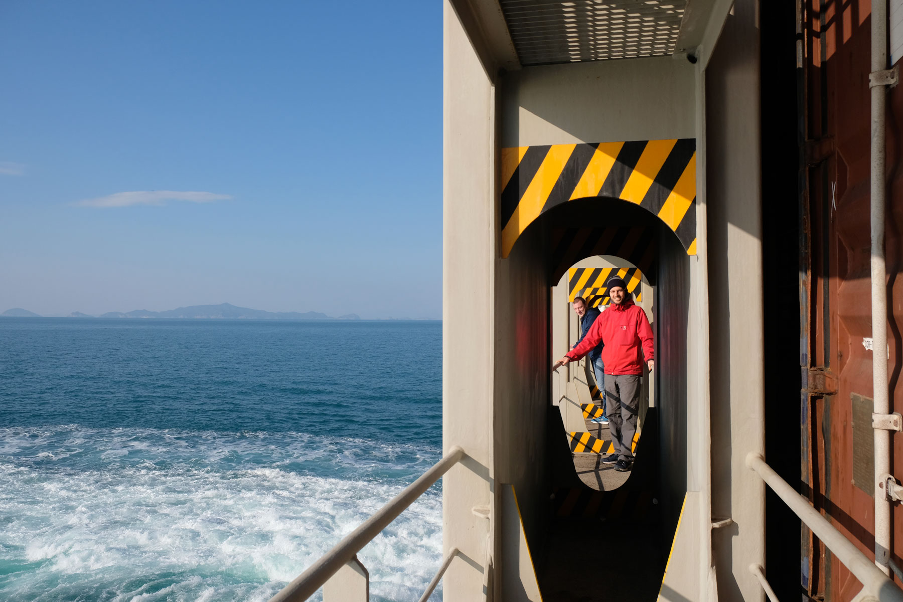 Sebastian am Heck eines Containerschiffes, das den Pazifik überquert.