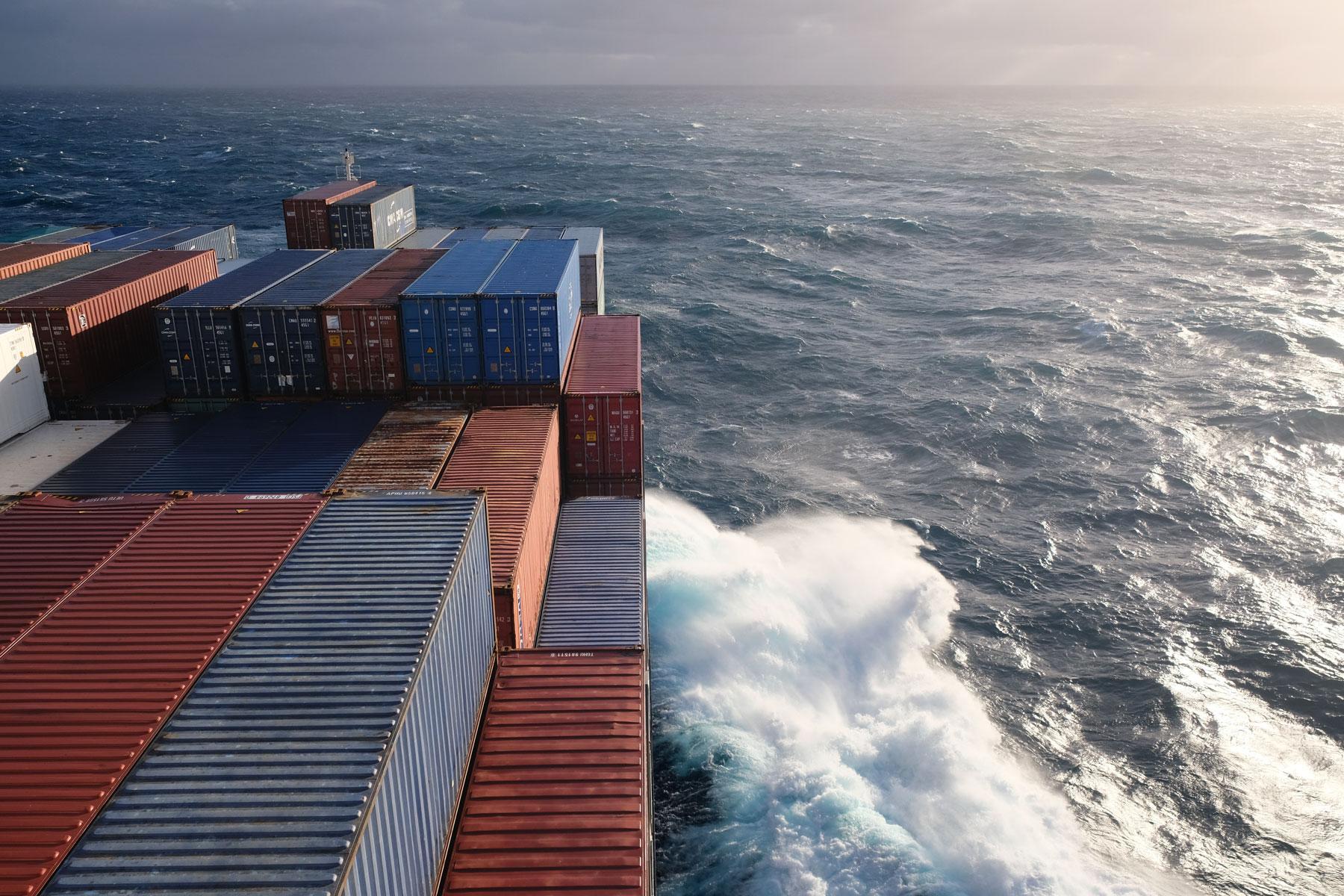 An der Seitenwand eines Frachtschiffes brechen sich die Wellen des Pazifiks.