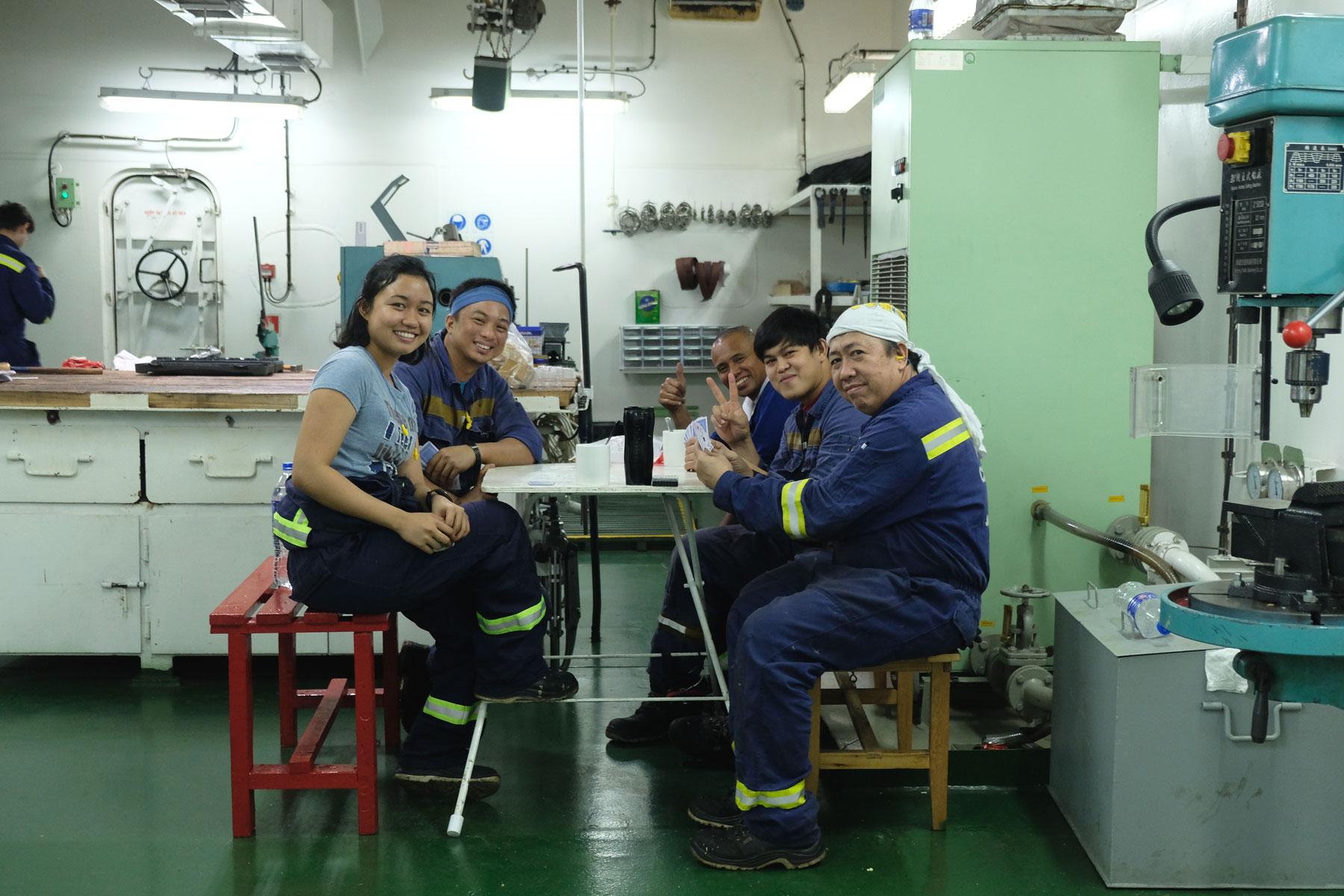 Die philippinische Besatzung eines Containerschiffs sitzt an eine Tisch.