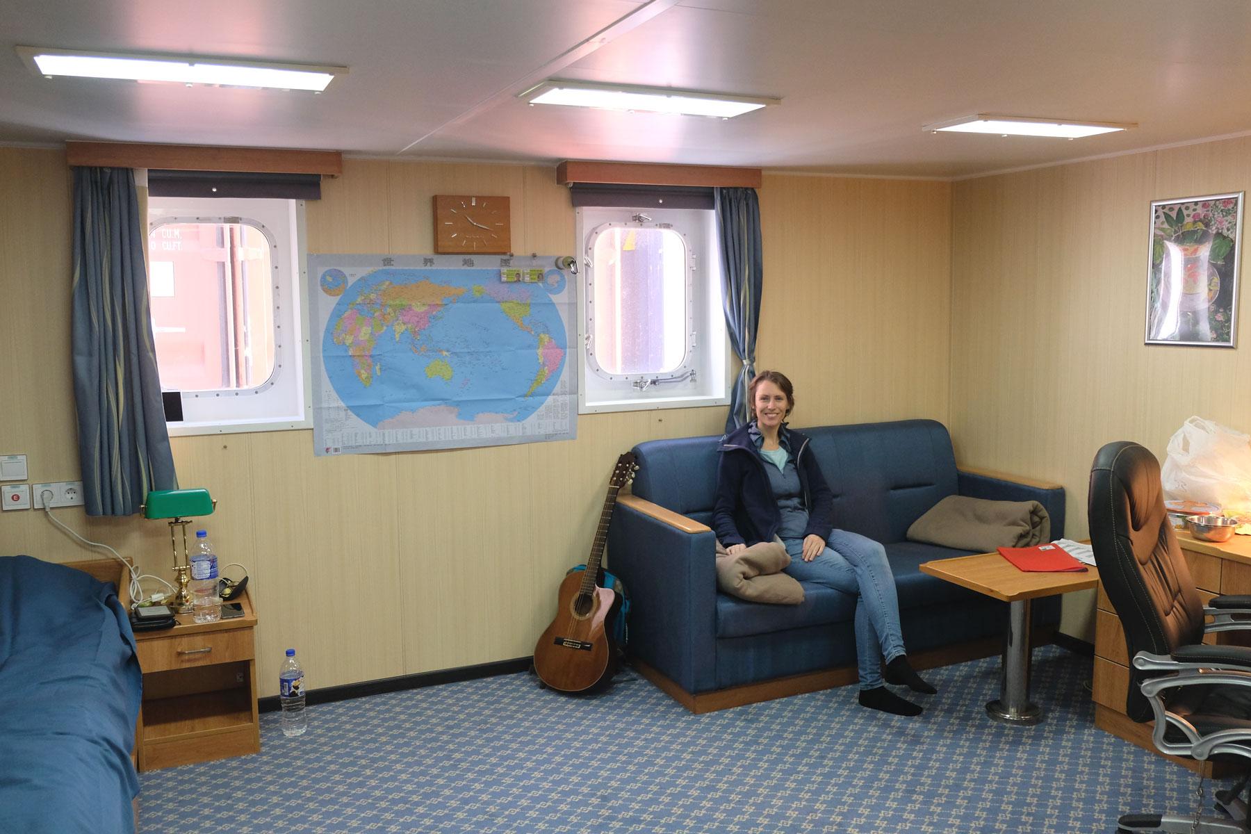 Leo sitzt in der Passagierkabine eines Frachtschiffs auf dem Sofa.