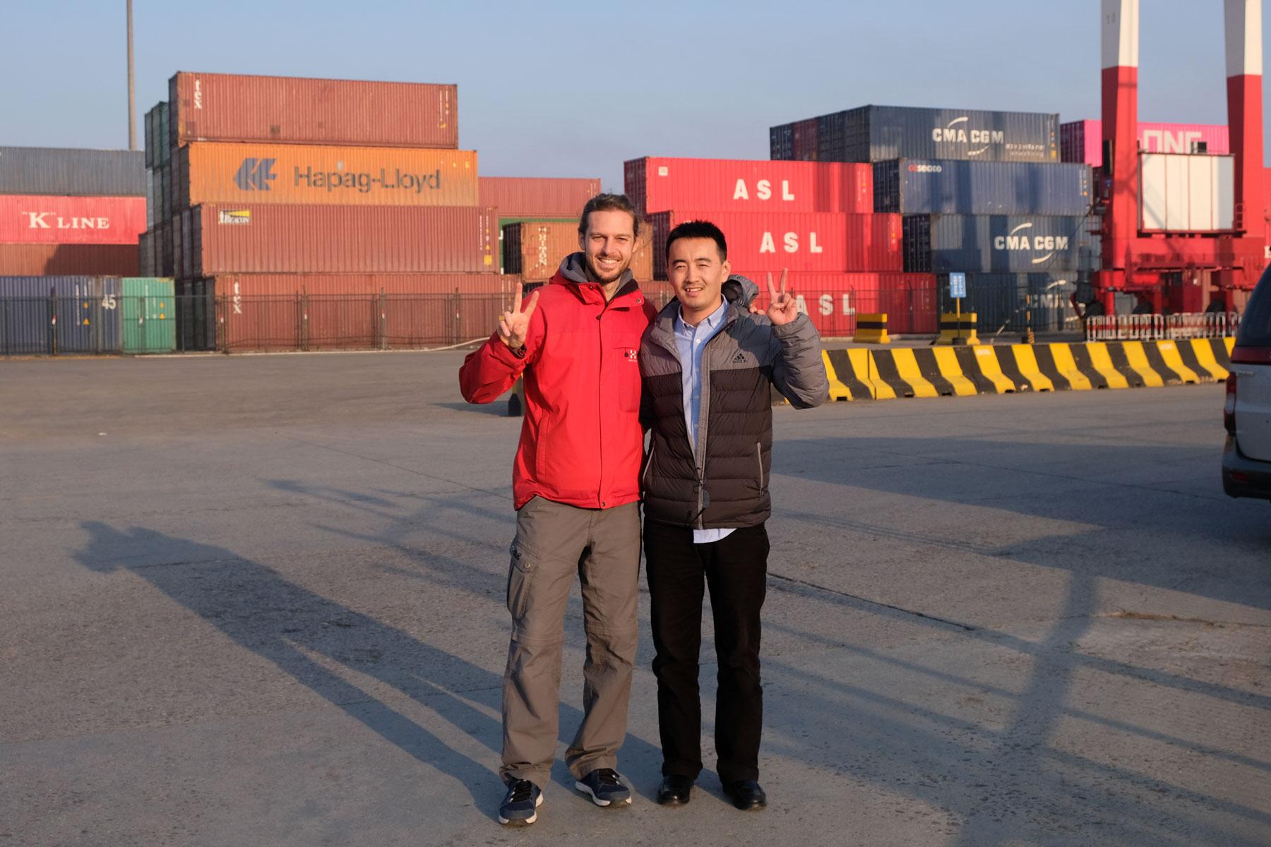 Sebastian mit einem Hafenagent am Hafen von Qingdao in China.