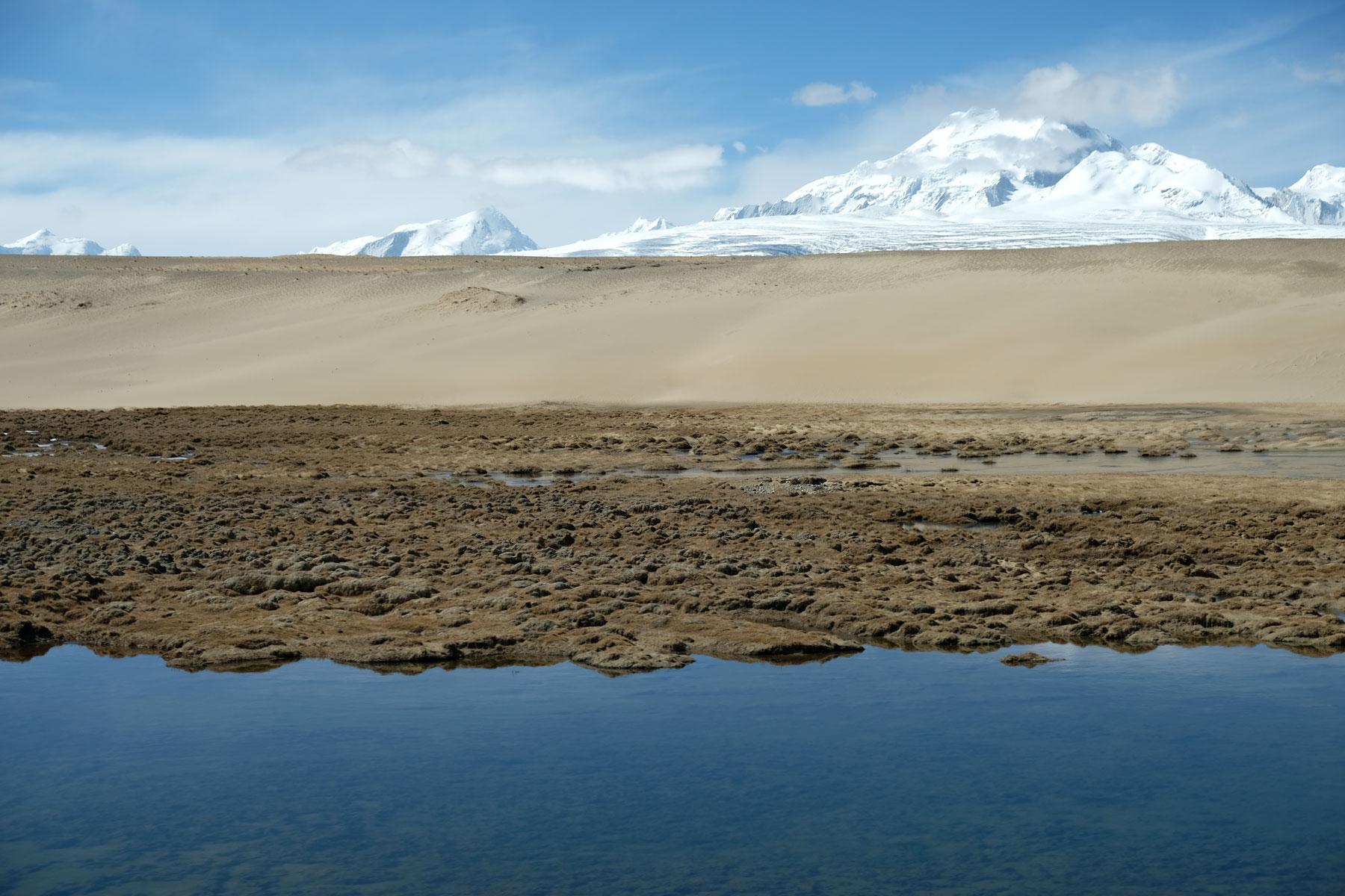 Ein kleiner See wird von Sanddünen abgelöst, die ihrerseits in Eisberge übergehen.