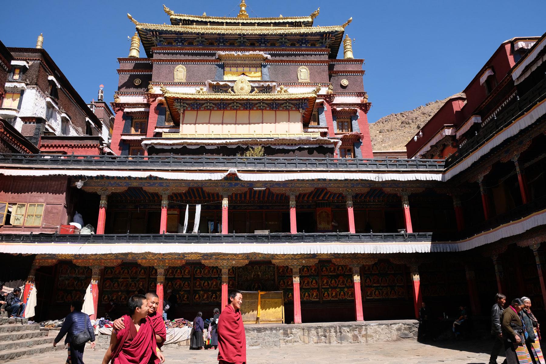 Drei Mönche laufen lachend über den Hof vor dem Haupthaus des Kloster Tashilunpo in Tibet.