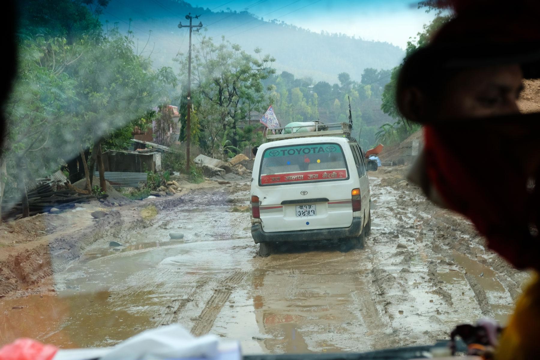 Ein Auto quält sich durch schlammige Straßen im Norden Nepals auf dem Weg an die tibetische Grenze.