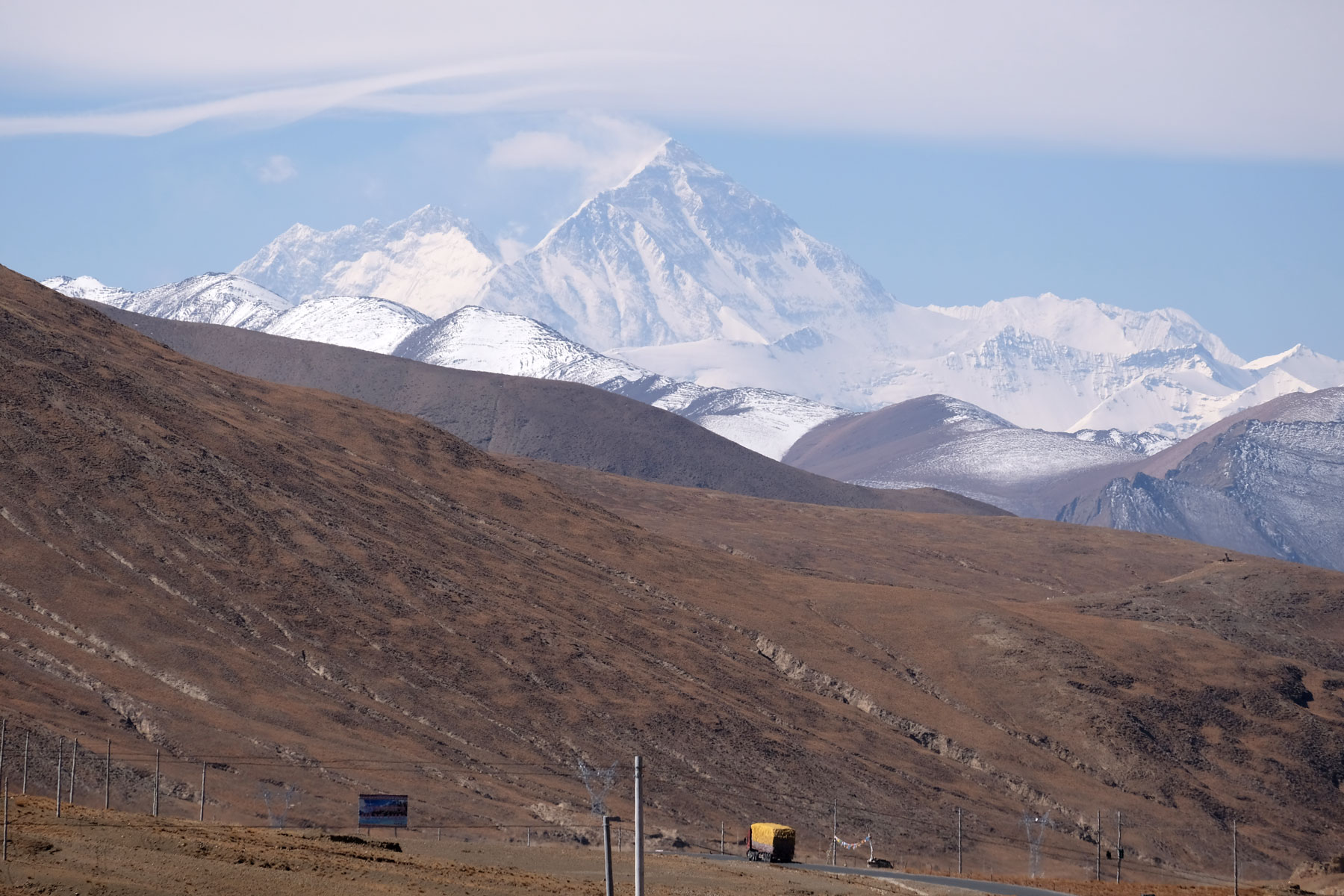 Ein Laster fährt auf dem Friendship Highway, im Hintergrund erheben sich die Berge.
