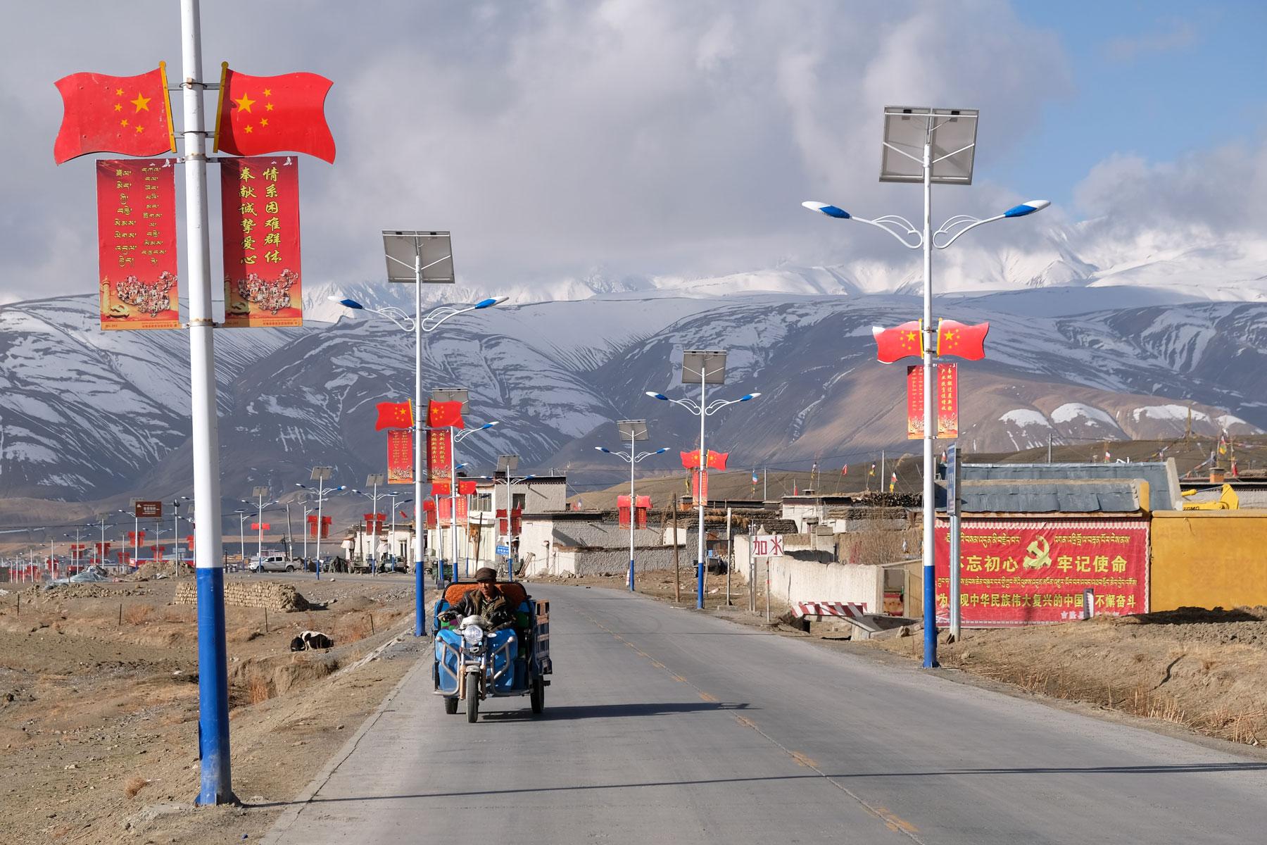 Ein Mann fährt mit seinem elektrischen Dreirad über eine Straße in Tibet, rechts und links von ihm chinesische Flaggen.