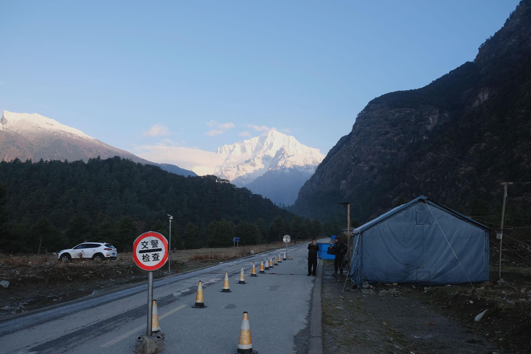 Eine Straßenkontrolle erscheint vor den ersten hohen Bergen Tibets.