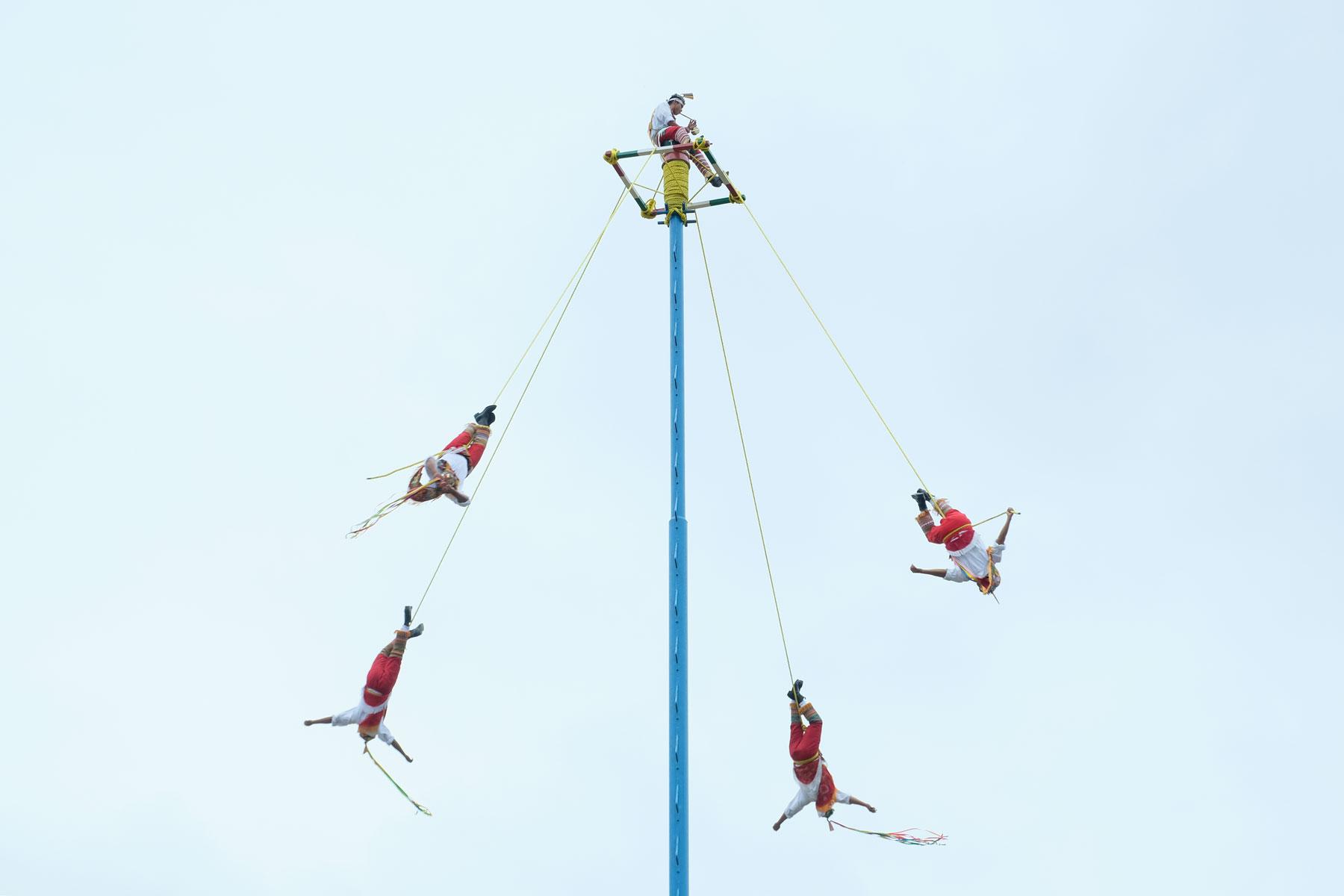 Fünf Voladores tanzen und schweben durch die Luft.