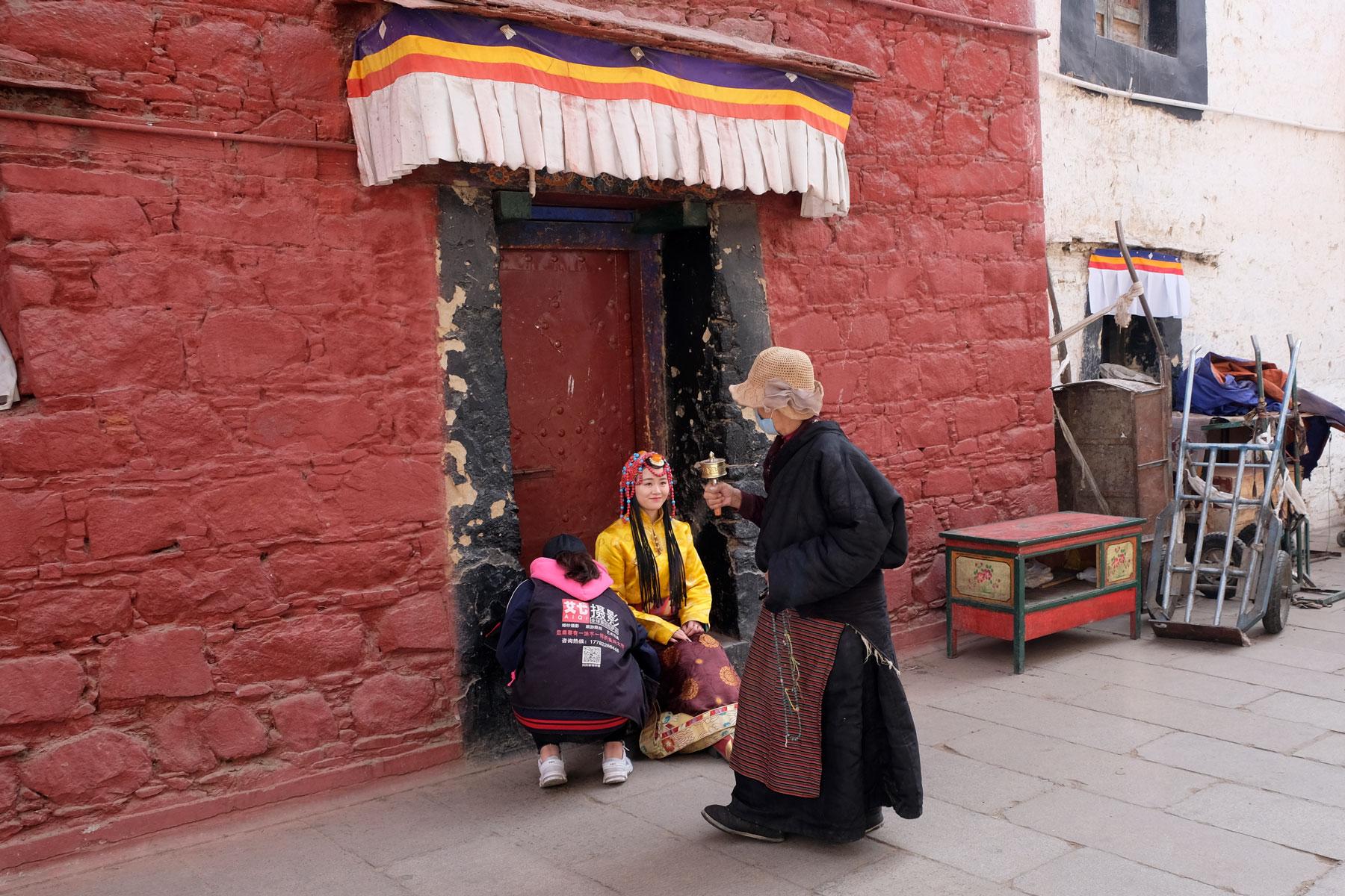 Eine Tibeterin läuft an einem Fotoshooting vorbei, bei dem sich eine Han-Chinesin in tibetischer Kleidung fotografieren lässt.