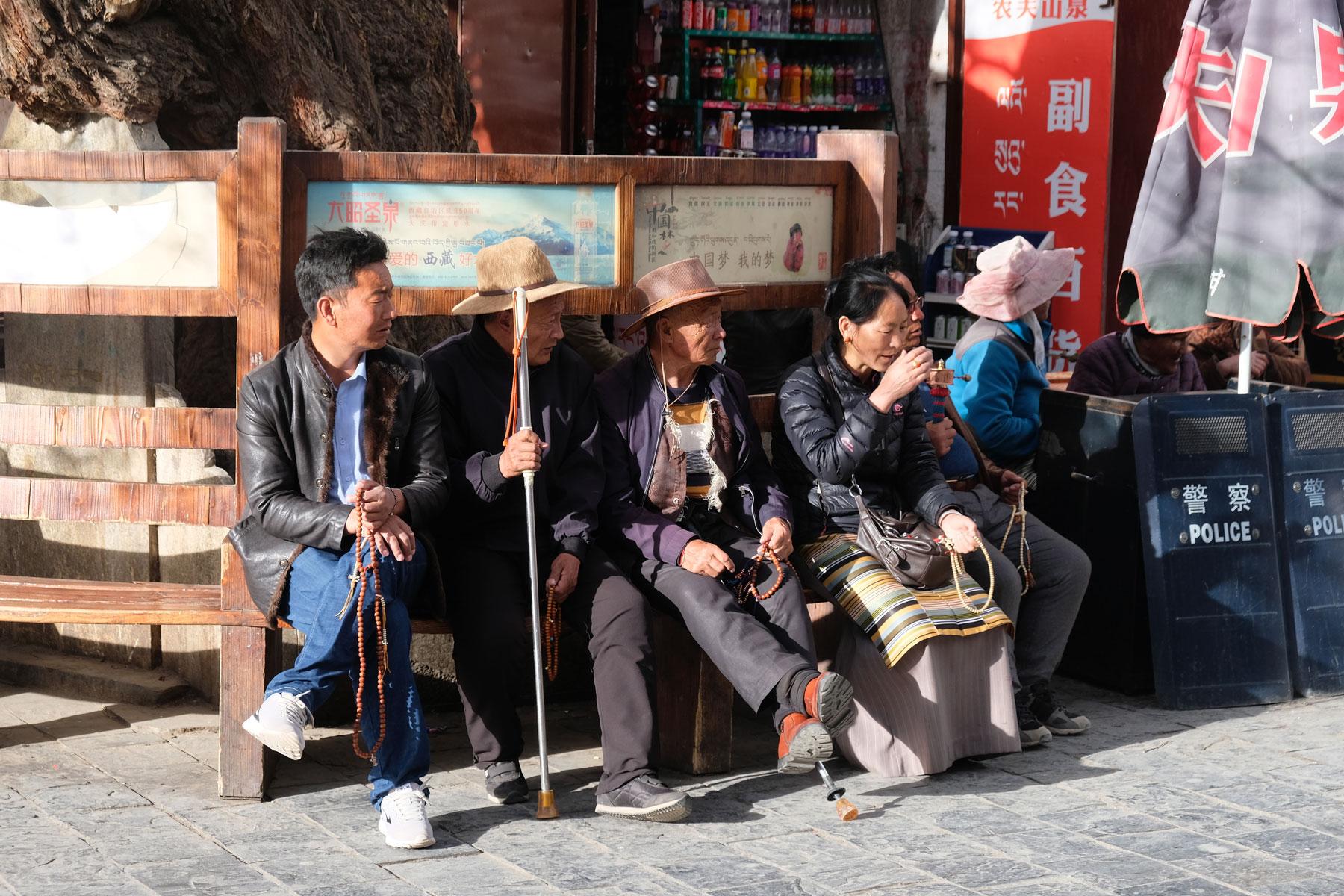 Eine Gruppe Tibeter sitzt am Rande des Barkhors in Lhasa in Tibet zusammen.