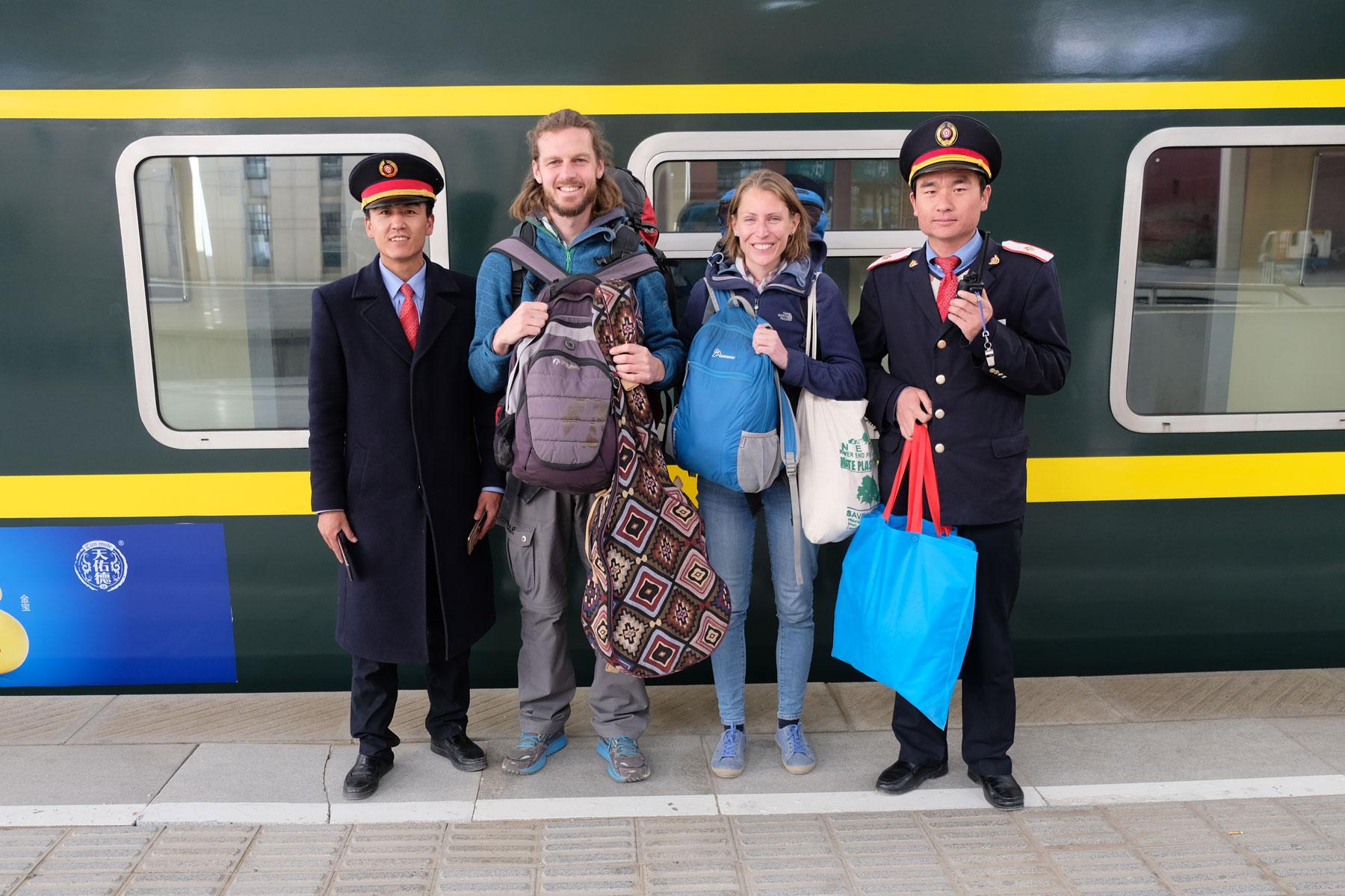 Leo und Sebastian stehen mit zwei Bahnhofsmitarbeitern vor ihrem Zug in Lhasa in Tibet.