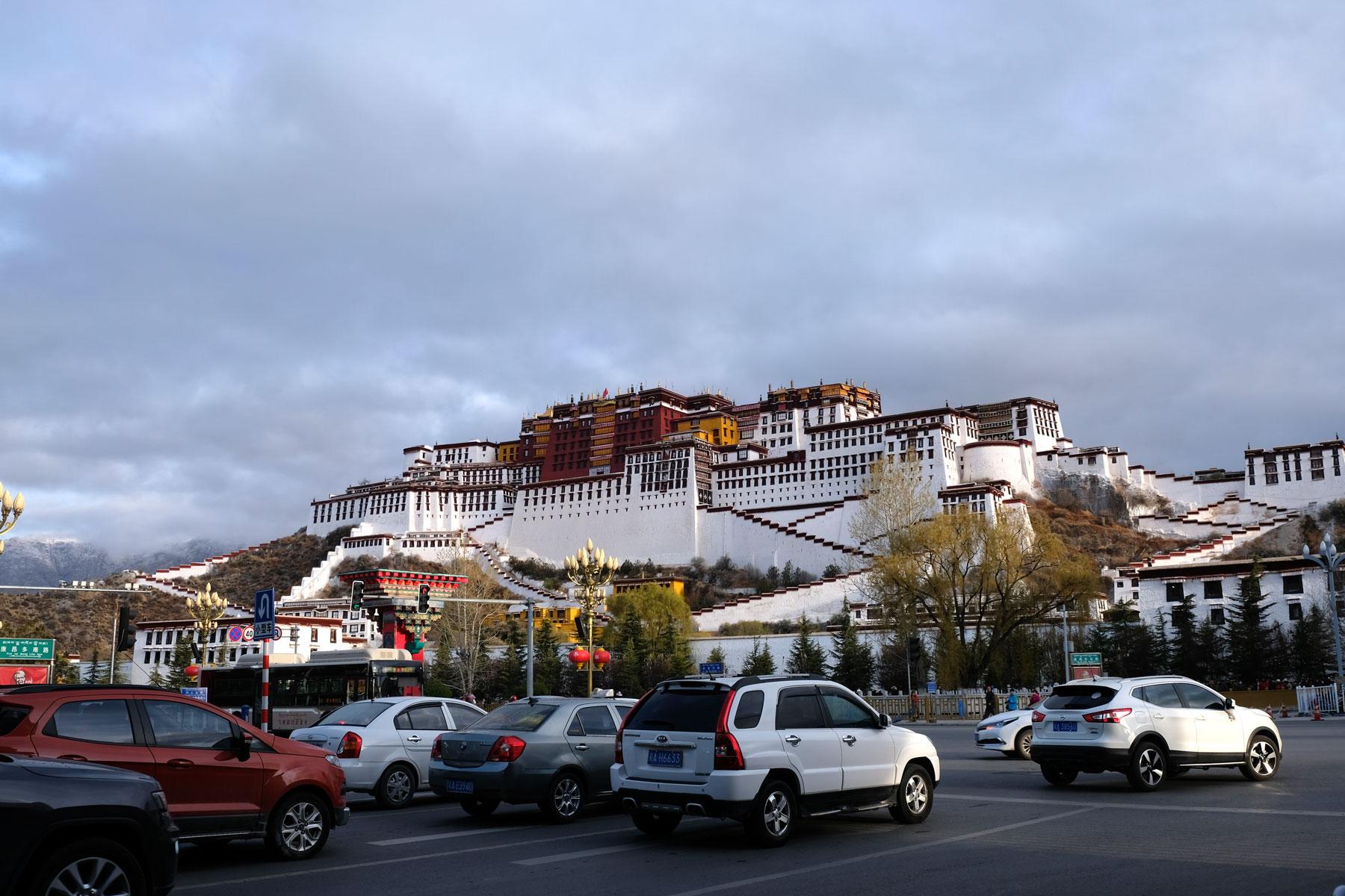 Autos stehen vor dem Potala-Palast in Lhasa in Tibet an der Ampel.