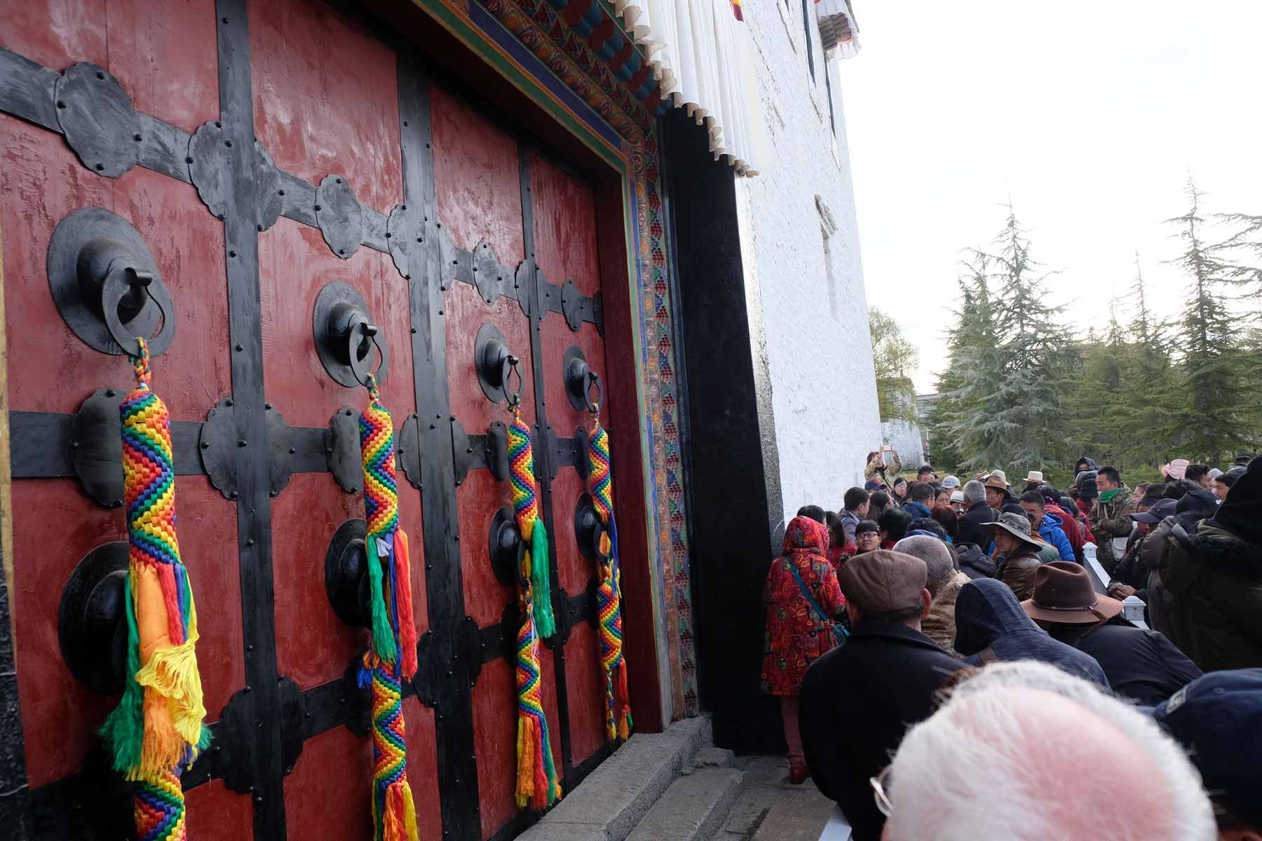 Wartende Menschen stehen vor den Toren des Potala-Palasts in Lhasa in Tibet.