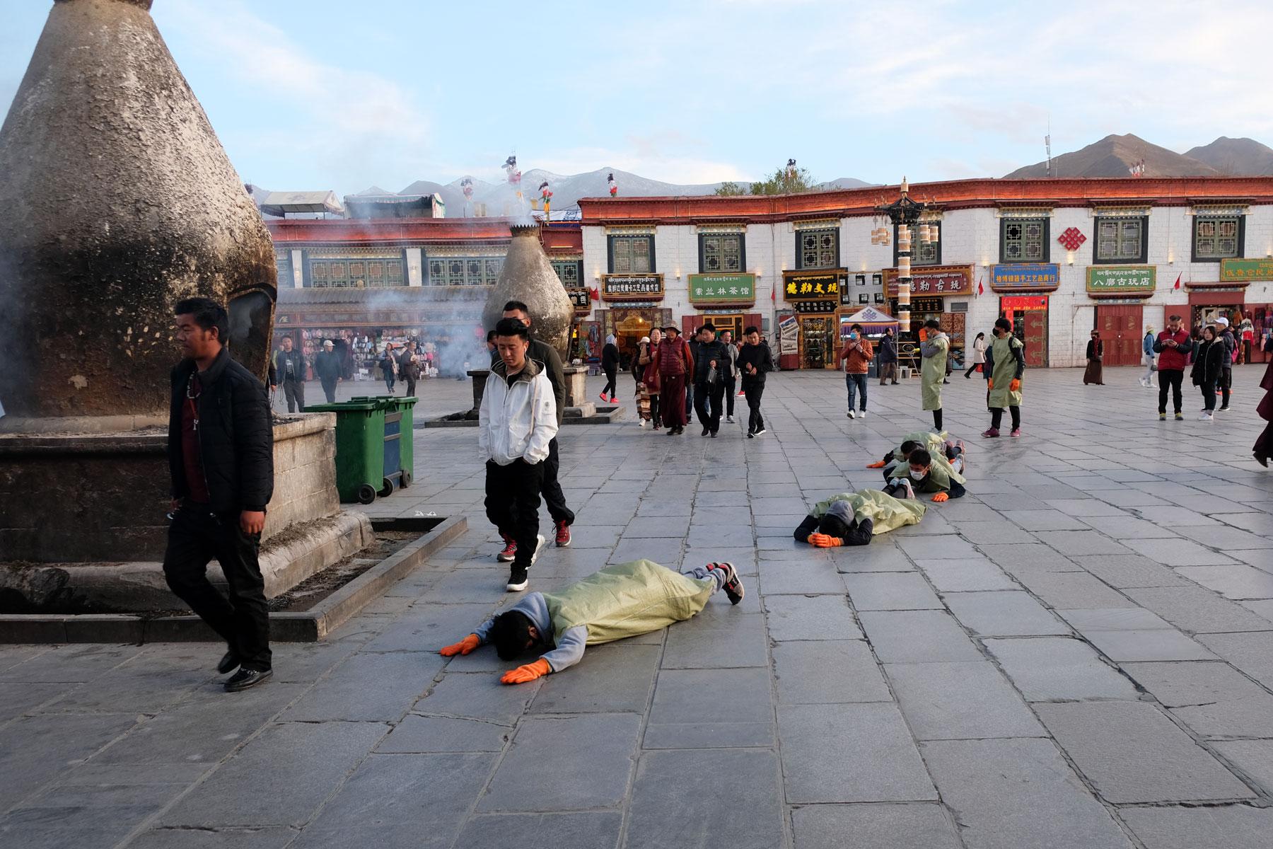 Eine Gruppe junger Tibeter betet auf dem Barkhor mit vollem Körpereinsatz.