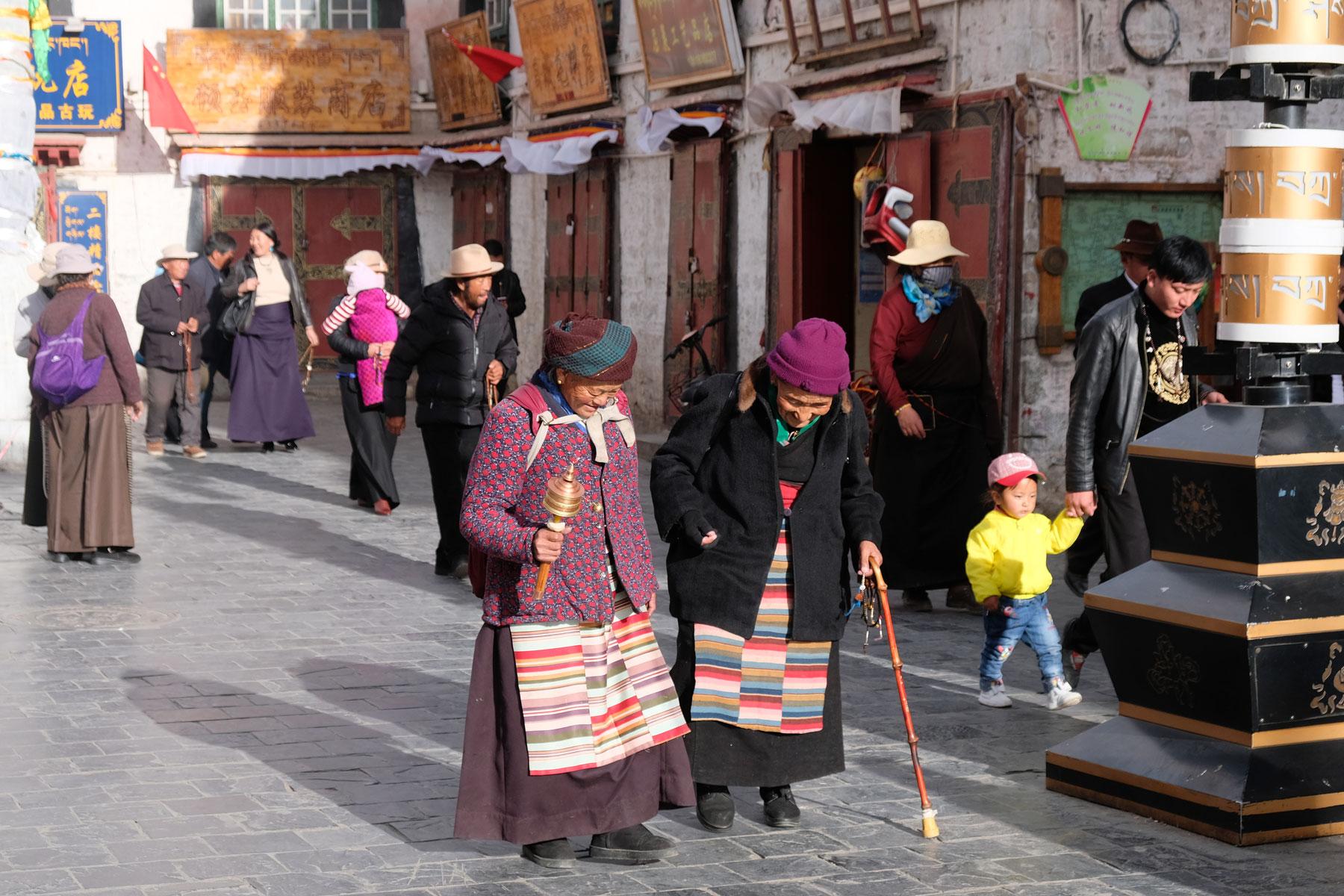 Zwei alte Tibeterinnen laufen gemeinsam den Barkhor in Lhasa in Tibet.