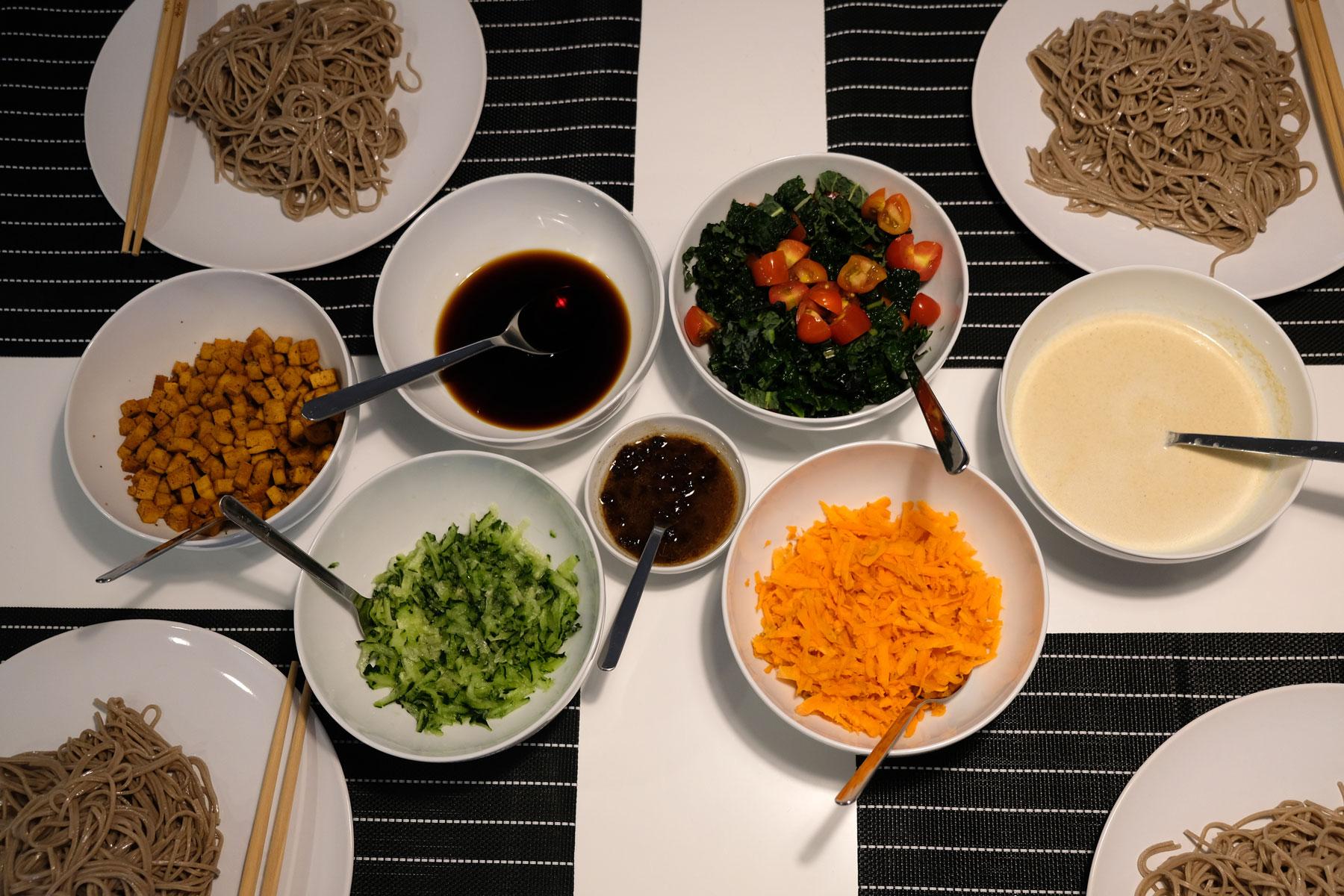 Auf dem Tisch stehen viele Schalen mit veganem Bio-Essen und Spaghetti.