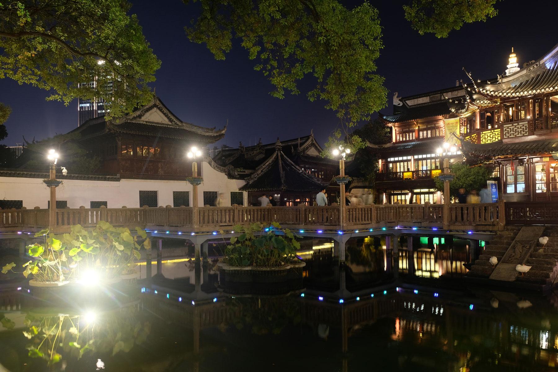 In der bei Nacht beleuchteten Altstadt von Shanghai spiegeln sich die Häuser im Wasser.
