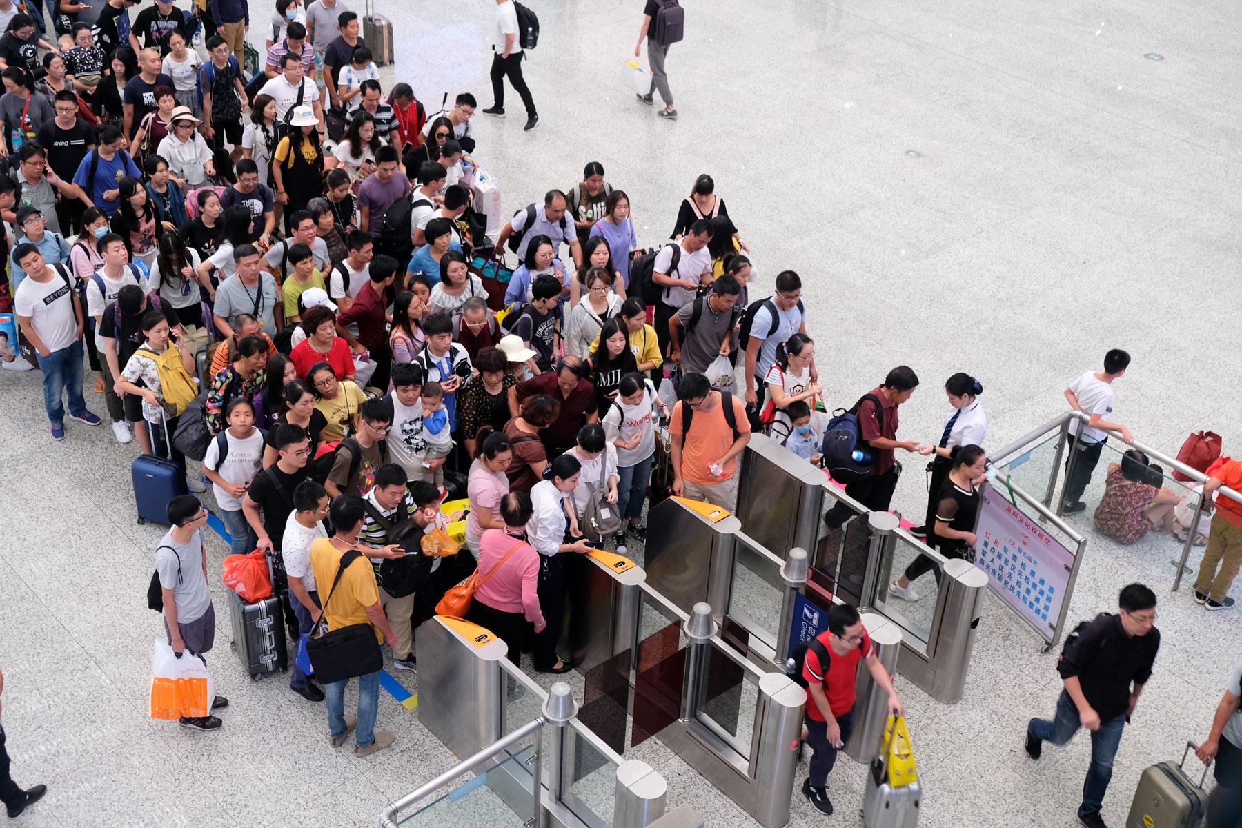 Menschen stehen in langen Schlangen vor den Eincheckschranken, um zu ihrem Zug in Nanning in China zu gelangen.